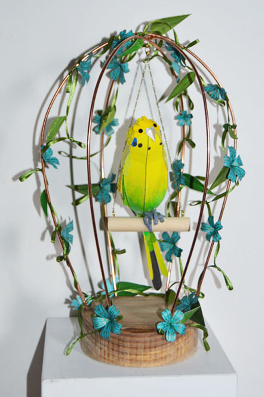 Sam the Budgie, in his bird cage adorned with blue flowers