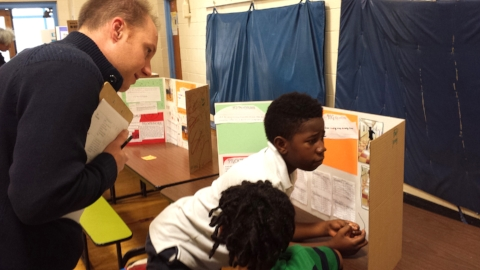 Kit Hagen, Vice President of Marketing and Strategy, looks on as a student describes his science fair project.
