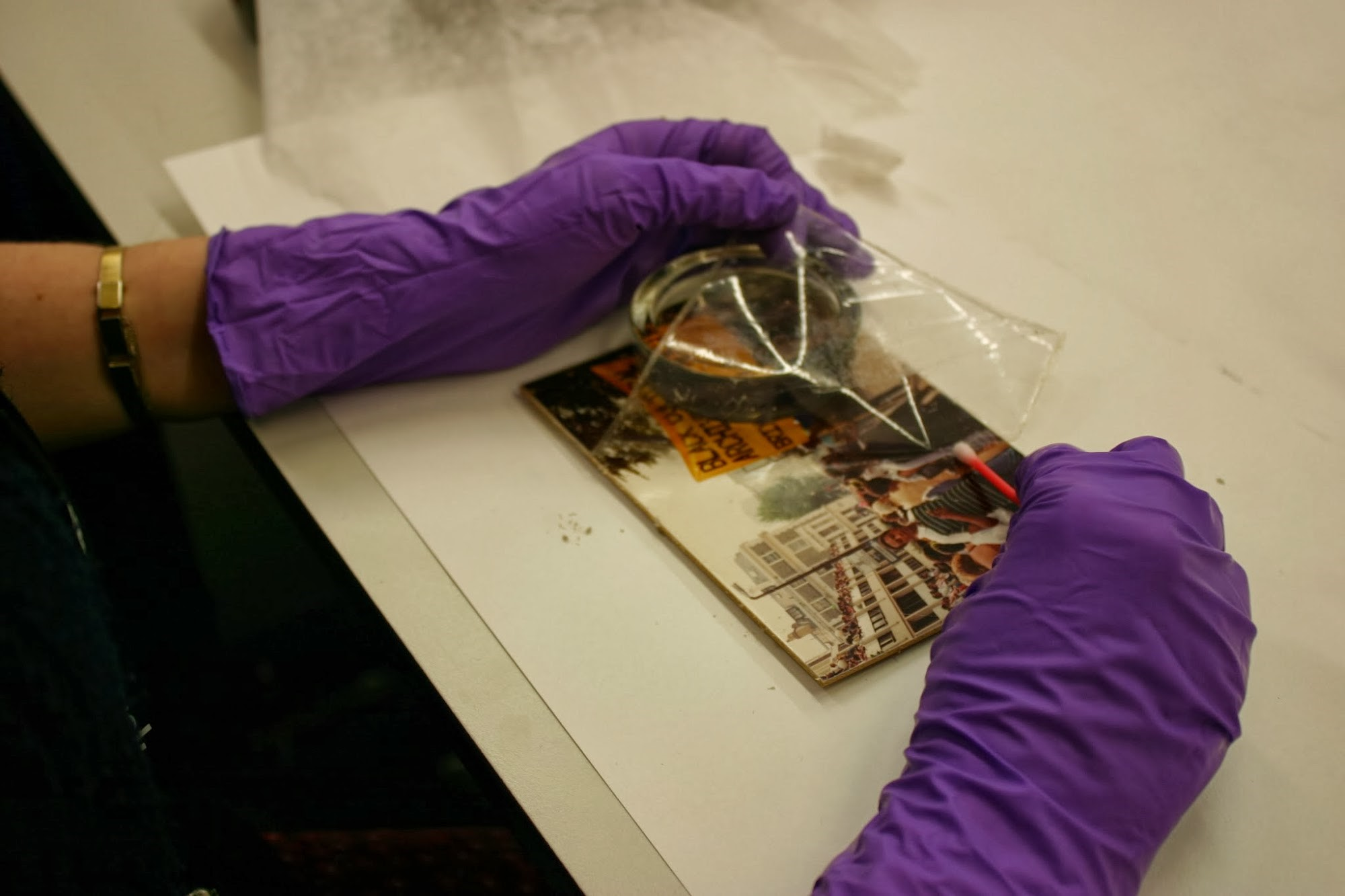 Using IMS and a cotton swab to gently peel the laminate carrier from the surface of the photographs.