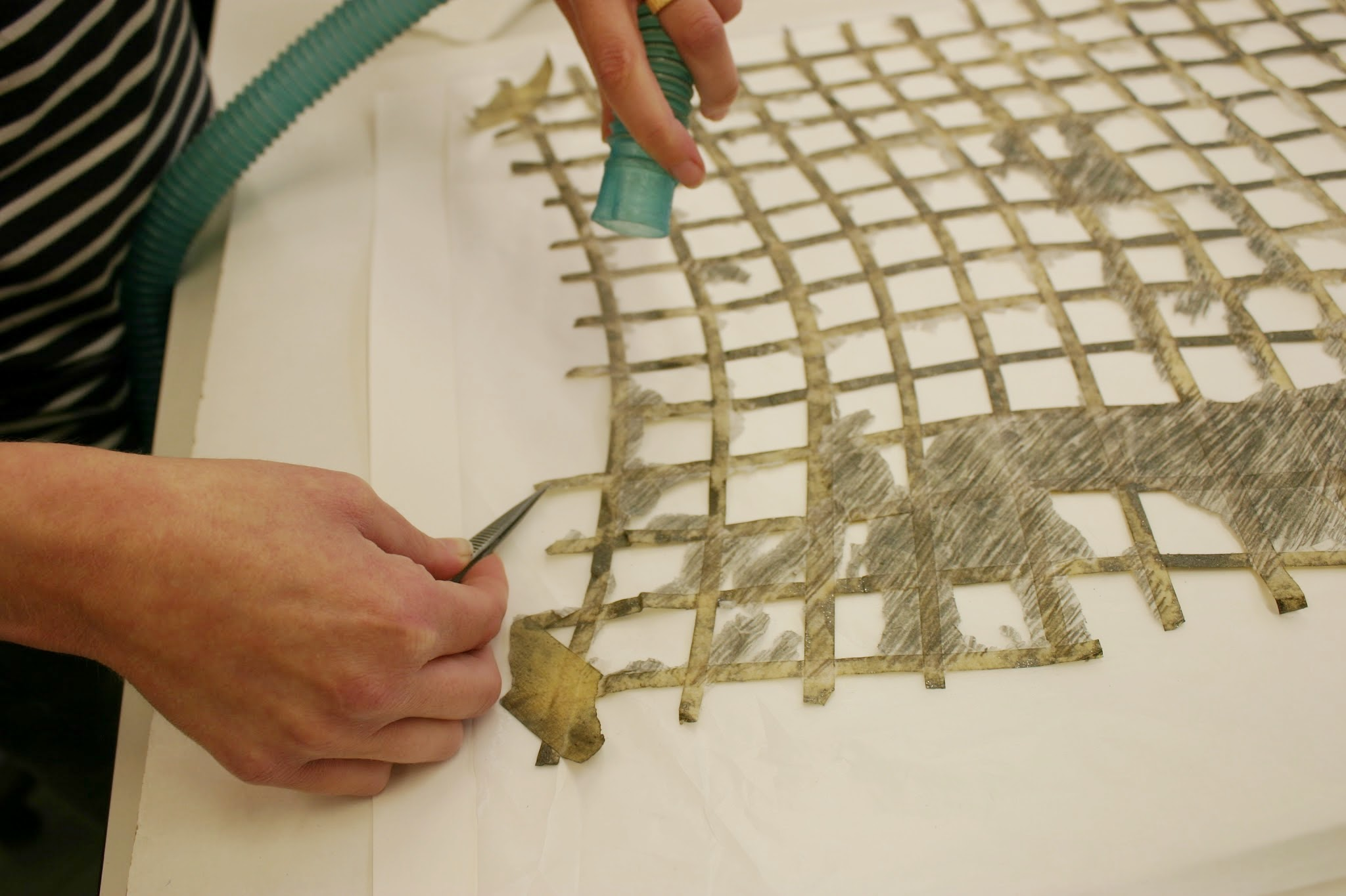 Humidification and flattening of creased masking tape and paper elements on the tape grid before reattachment.