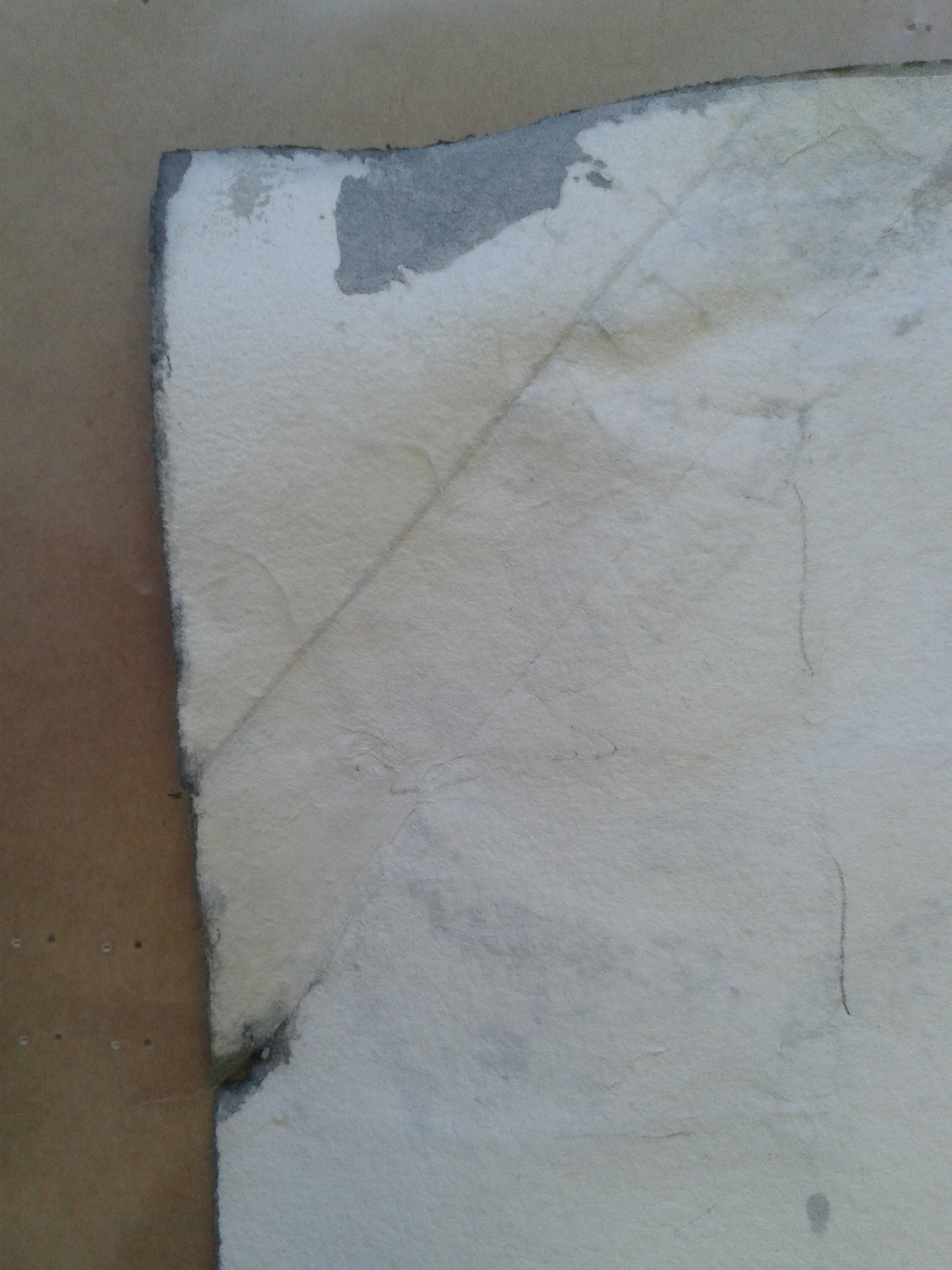 Detail of upper right corner prior to treatment.  The artist or an assistant had previously repaired a crease with heavy paper.