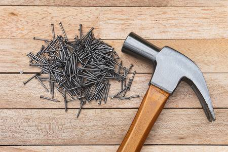 43538229-hammer-and-nails-on-wood-background.jpg