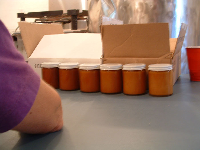 The jars on the right have lightened in color as the crystallization process occurs, making the spreadable maple cream.