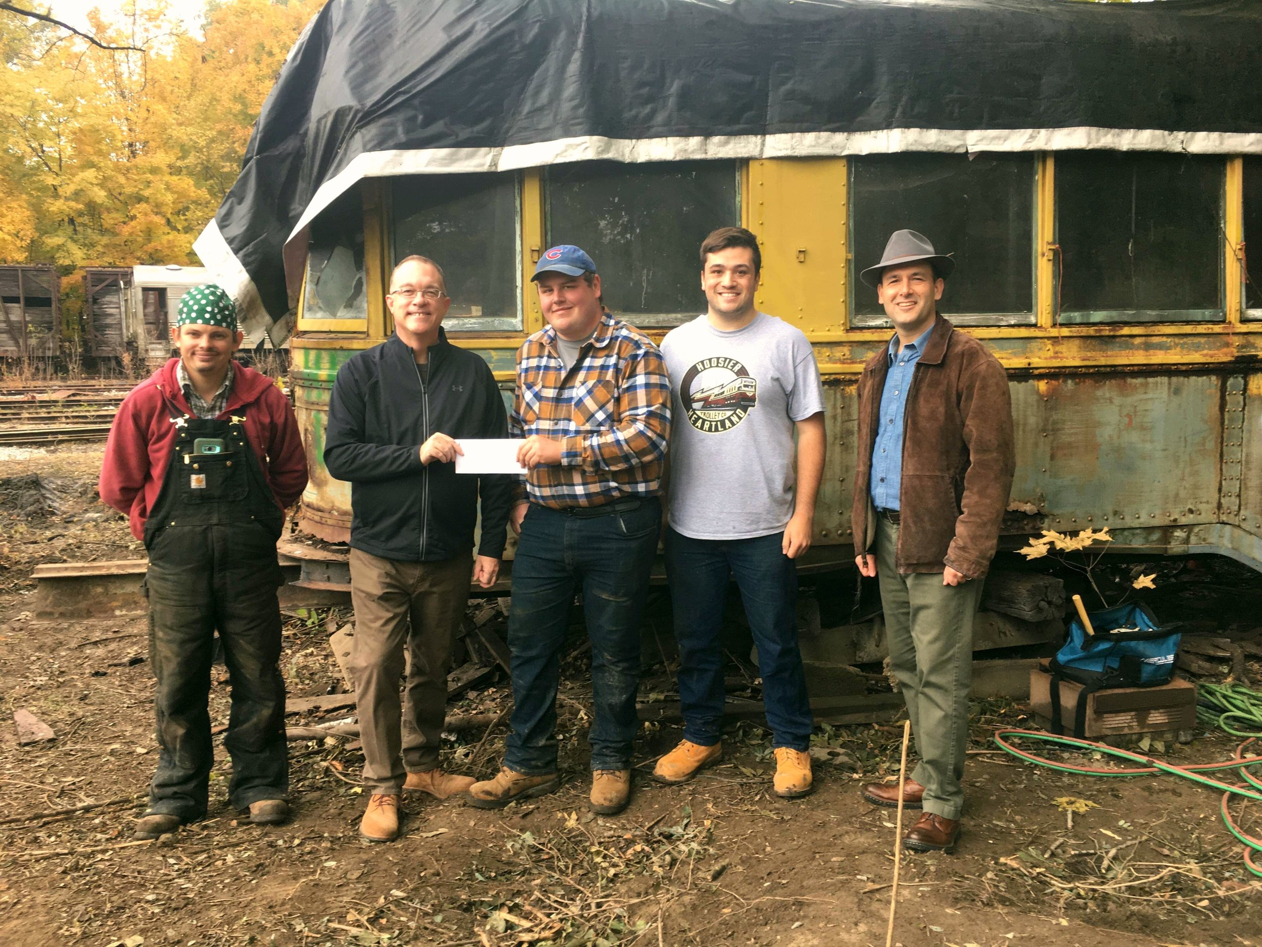 Indiana Landmarks Vice President of Preservation Services Mark Dollase presents the grant letter and check to Hoosier Heartland Trolley Company Secretary William Whitmer at Forest Park in front of the last Indianapolis streetcar on Saturday, October 27, 2018.     Left to Right:    HHTC Treasurer Jakob Stage, Indiana Landmarks Vice President of Preservation Services Mark Dollase, HHTC Secretary William Whitmer and Vice President Cameron Nichols, and City of Noblesville Deputy Mayor Steve Cooke.