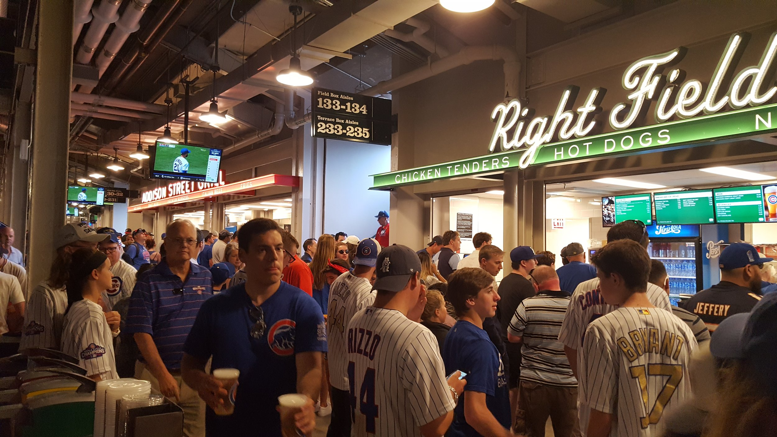 Fans crowded into the concessions area between innings, many spending the entire break in line. Those still in line after gameplay resumed kept their eyes on the overhead screens, and loud reactions from the stands caused visible frustration.