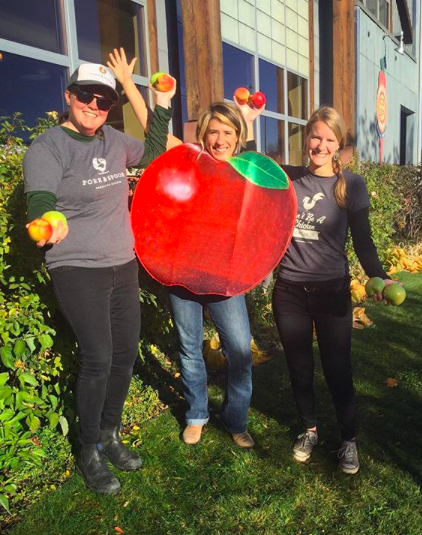 Jacqui, Leah, and Chelsea celebrating Fork & Spoon's Apple-a-Day month at the Community Food Co-op last November.
