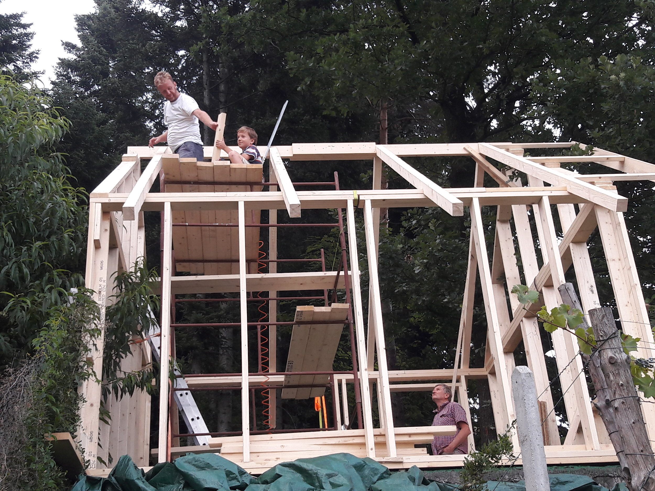 Michal building an apiary workshop with his father and son