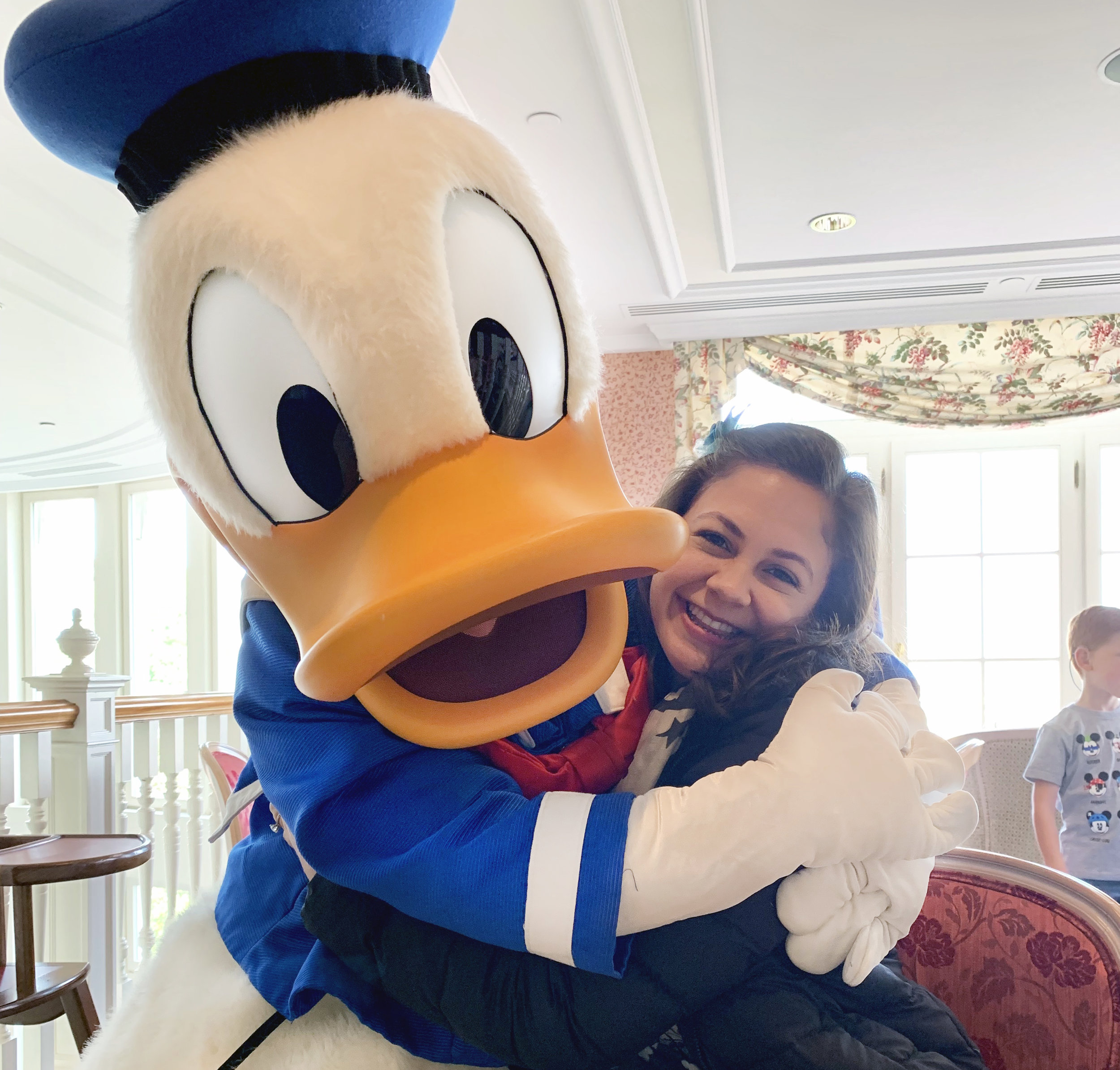 Andrea posing with Donald Duck in Disneyland Paris.