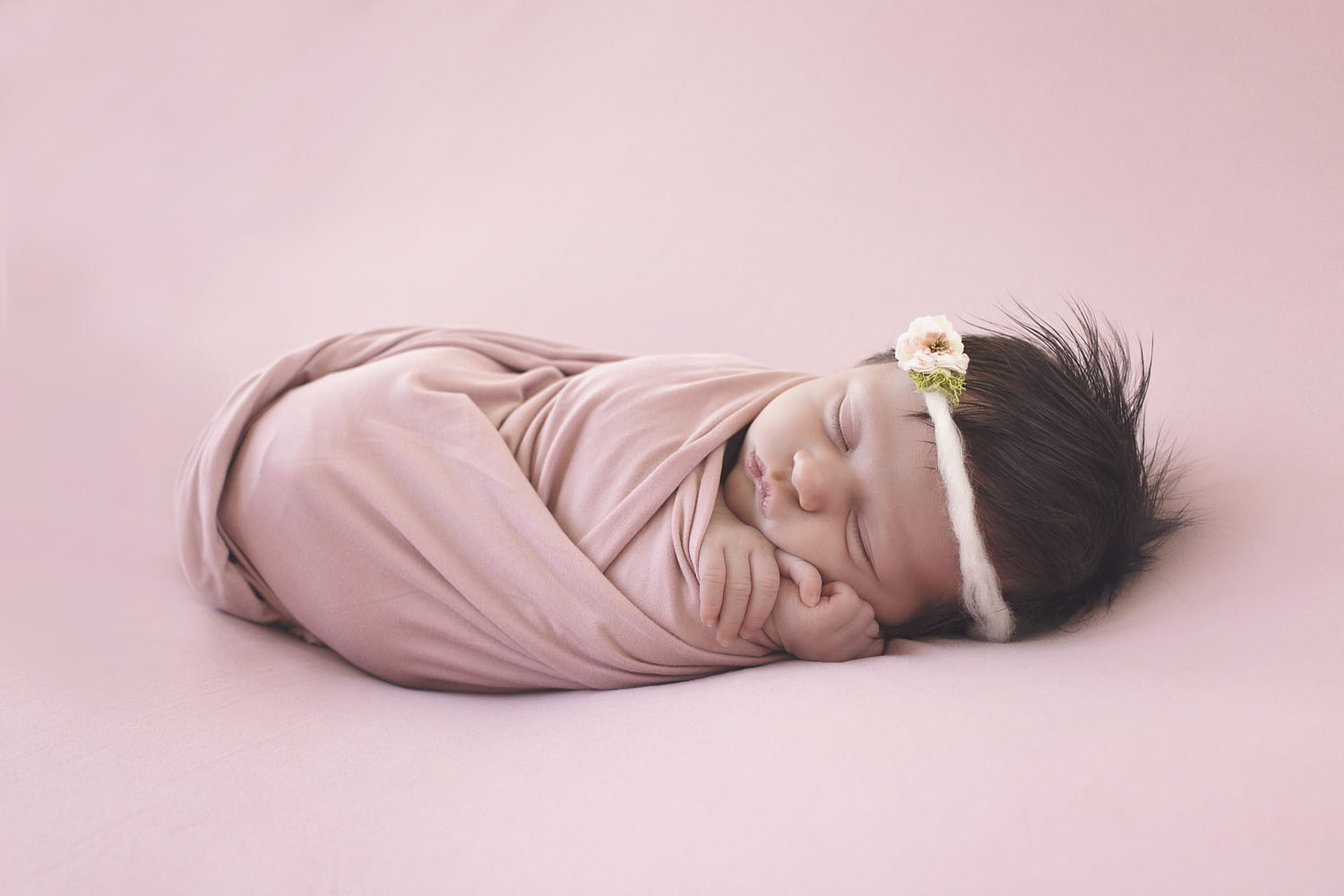newborn photography of sleeping baby girl wrapped in pink and with a pink flower headband