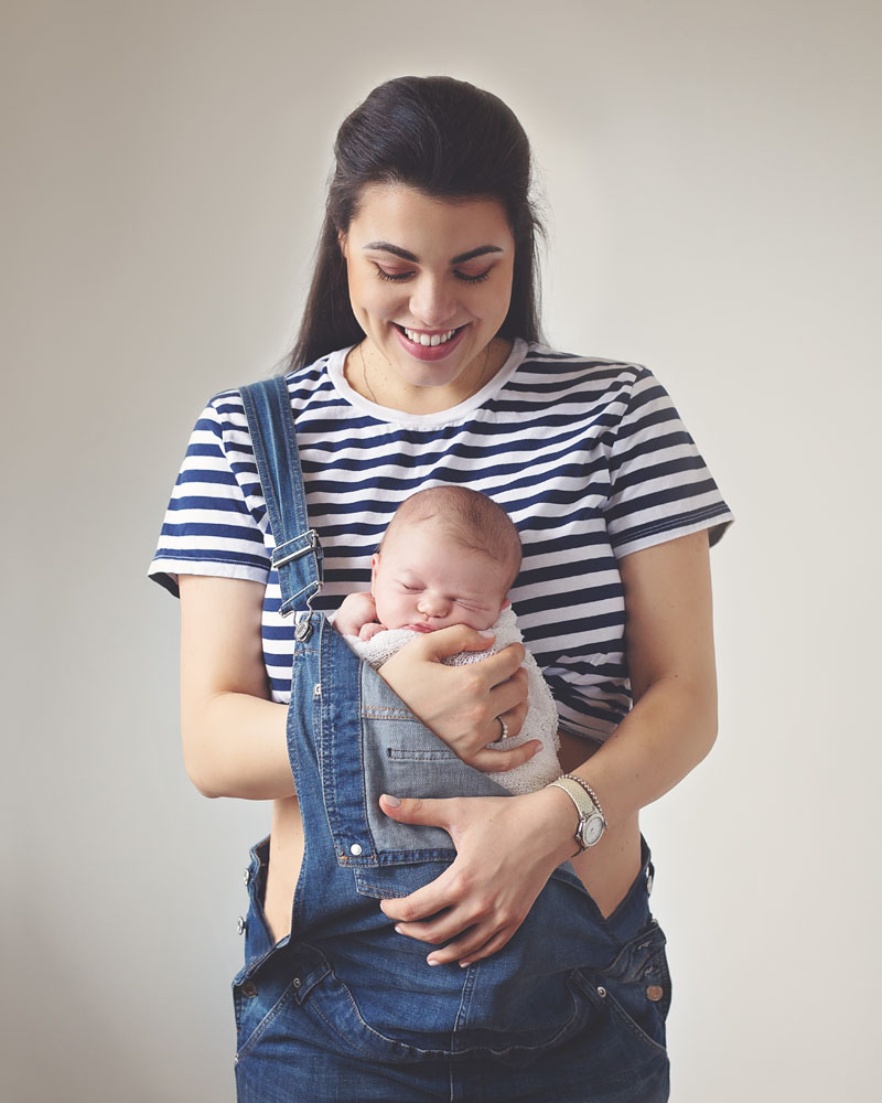 mother wearing overalls with her newborn baby inside