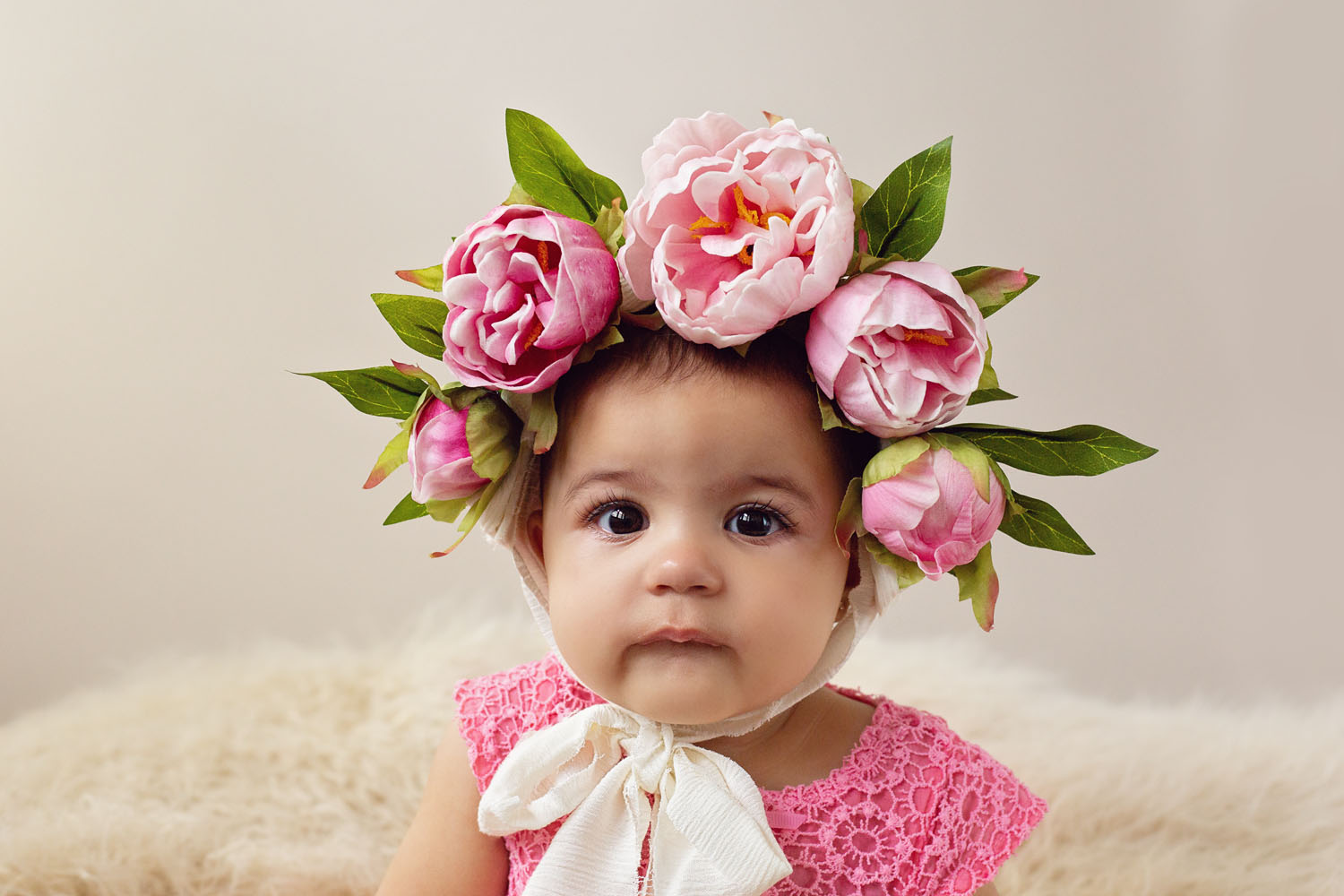 6 month old milestone photograph of baby girl sitting with flowers on her head