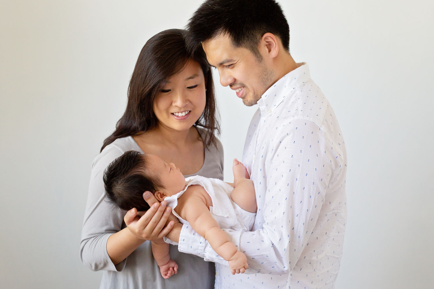 professional photos of a beautiful couple smiling at their newborn baby girl in kearny new jersey