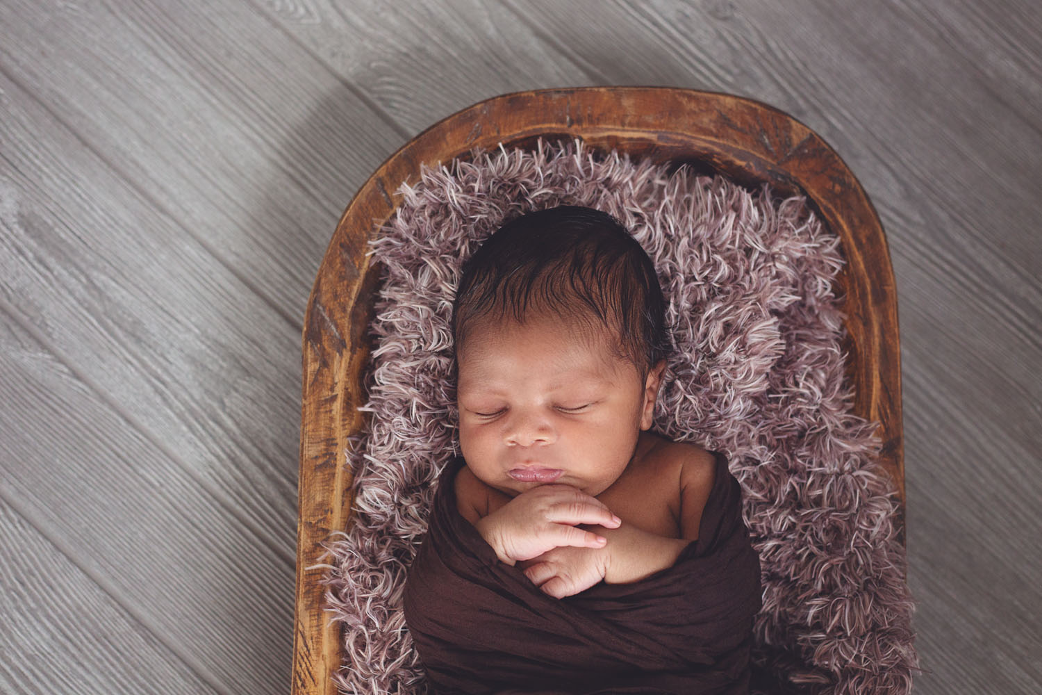 newborn photography in new jersey of a baby boy sleeping in a wood basket