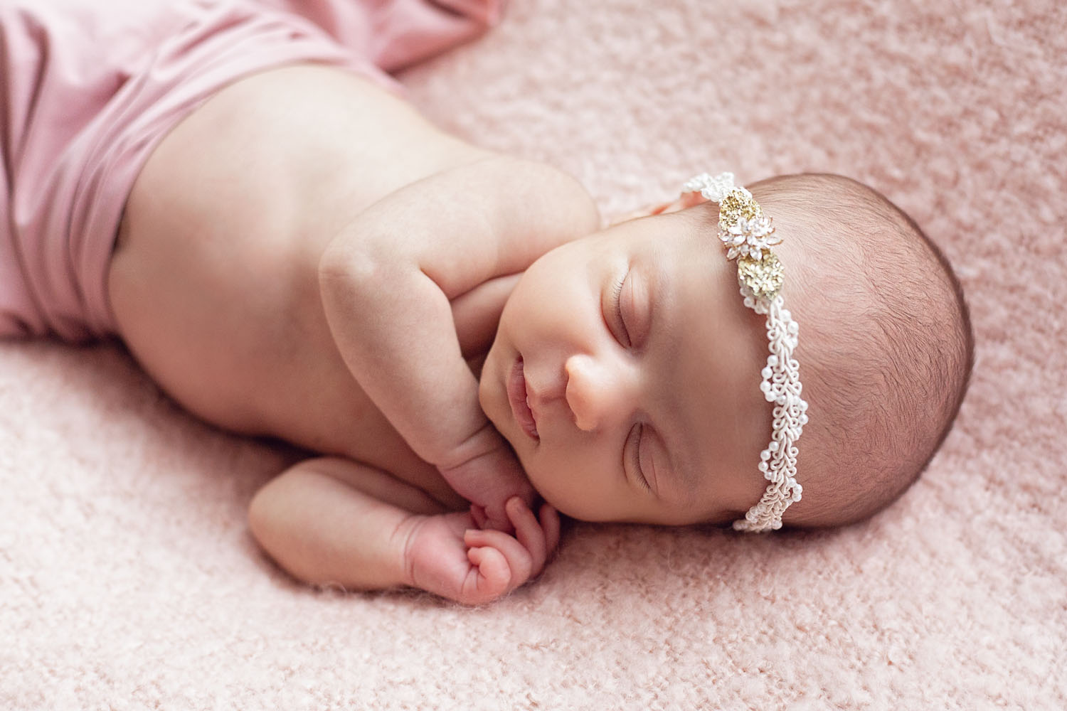 Newborn photography in new jersey of a baby girl on a pink blanket with a jewel headband in nutley
