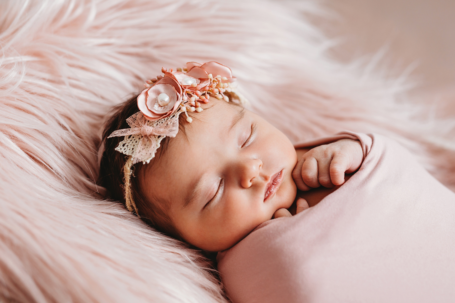 newborn photographer of a baby girl with a pink swaddle and a pink headband in new jersey