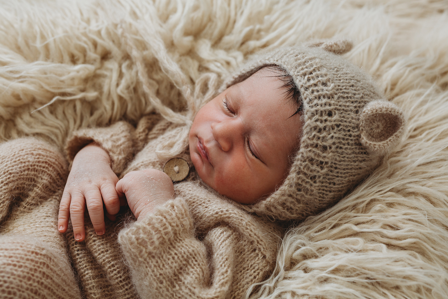 Newborn photography in rutherford nj of a sleeping baby boy in a teddy bear outfit