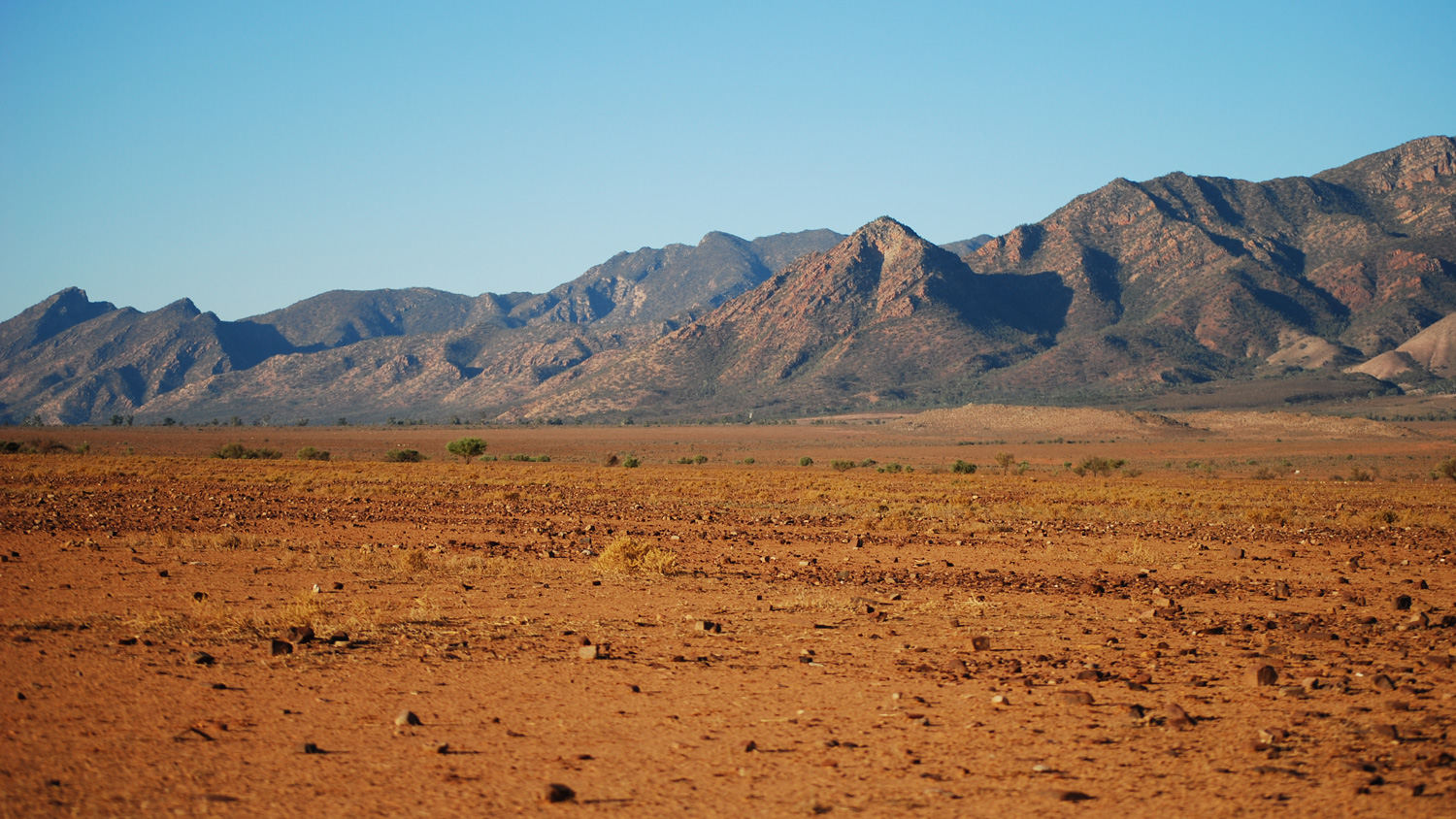 The Australian continent is largely covered by transported sediments (foreground) that have been eroded over millions of years from elevated rock sequences nearby (background), as shown here in the Flinders Ranges, South Australia example. Geologists must search below these cover rock sequences for mineral deposits using expensive drilling and geophysical techniques that are available today. Image:  Peripitus .