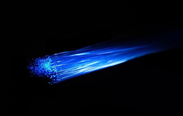 Blue light illuminates the thin glass threads of a fibre optic cable. Each cable is able to transport light/information across long distances via internal reflection (similar to the way a mirror can direct light). To find out more check out:  Fiber optic cables: How they work.  Photo by Compare Fibre on  Unsplash .