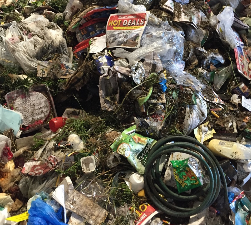 A sample of landfill waste from a town in the Macedon Ranges: green waste present throughout, food sealed in containers, recyclable containers, paper, cardboard and soft plastics present.