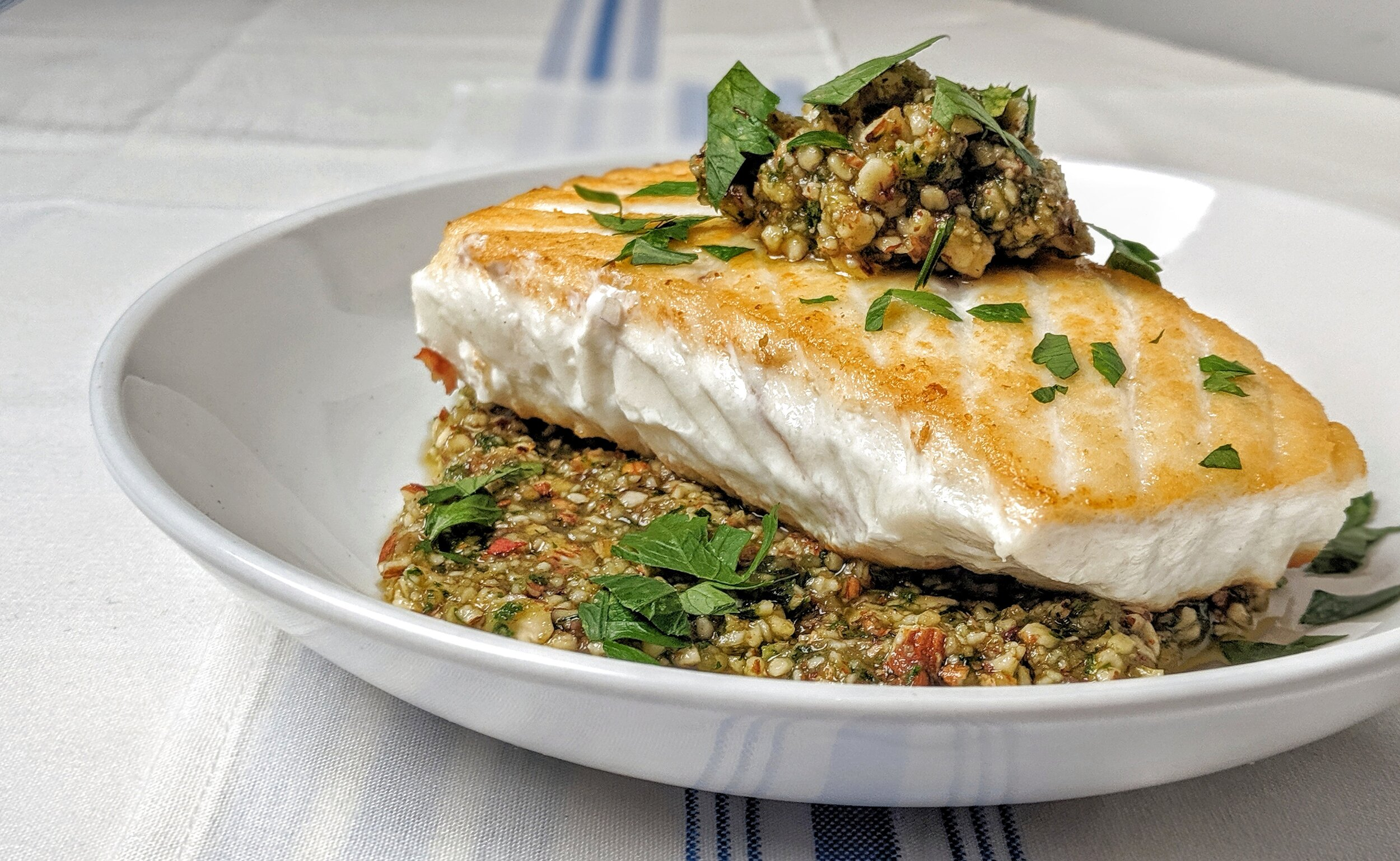"""What We're Cooking - We recently got the pleasure of participating in the Sitka Salmon Shares annual recipe contest as judges! We made Halibut with Almond & Parsley Pesto.If you haven't tried Sitka Salmon Shares yet use the code """"MMJD19"""" for $25 off your order.Recipe for Halibut with Almond & Parsley PestoIngredients:For the Halibut1 fillet Halibut, cut into 1 inch pieces1 tablespoon coconut oilFor the Sauce1/3 cup of almonds toasted until fragrant and has a little color then let cool1 teaspoons anchovy paste2 garlic cloves2 tablespoons good quality coconut oil1/3 cup extra virgin olive oil1 1/2 teaspoons red wine vinegar2 tablespoons of flat leaf parsley1 teaspoon red chili flakessea salt and fresh ground pepperInstructions:Sear the Halibut in a saute pan until cooked through.Add all of the Sauce ingredients to a food processor and process until somewhat smooth.Serve the sauce over the fish."""