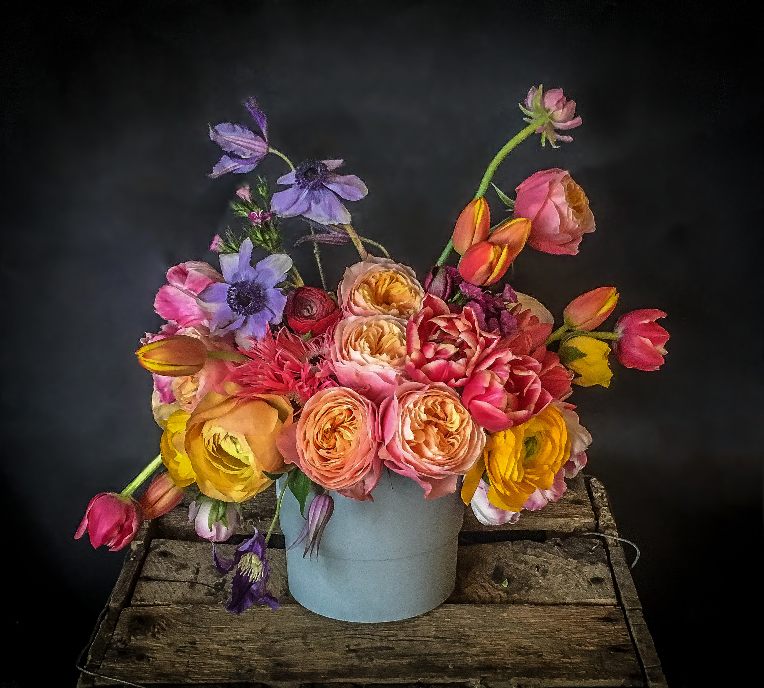 Floral design of bright blooms which include peonies, roses, tulips, anemone in a concrete pot. Local florist Bath uk