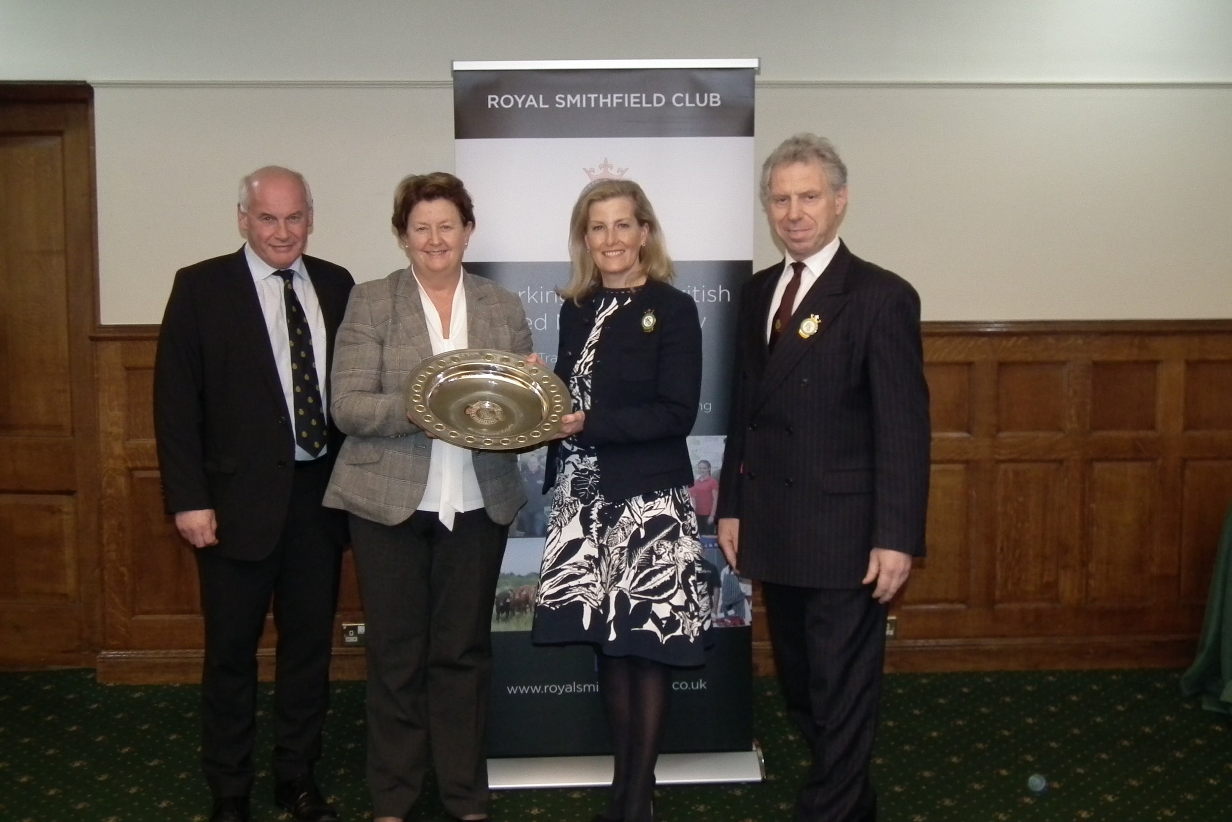 Her Royal Highness The Countess of Wessex presenting the Royal Smithfield Bicentenary Trophy to the 2018/19 winner Mrs Heather Jenkins in recognition of her major contribution to the British livestock industry over the past thirty years. Pictured (far left) is David Gunner, Joint Chief Executive Dovecote Park Ltd and (far right) William Bedell, Chairman Royal Smithfield Club