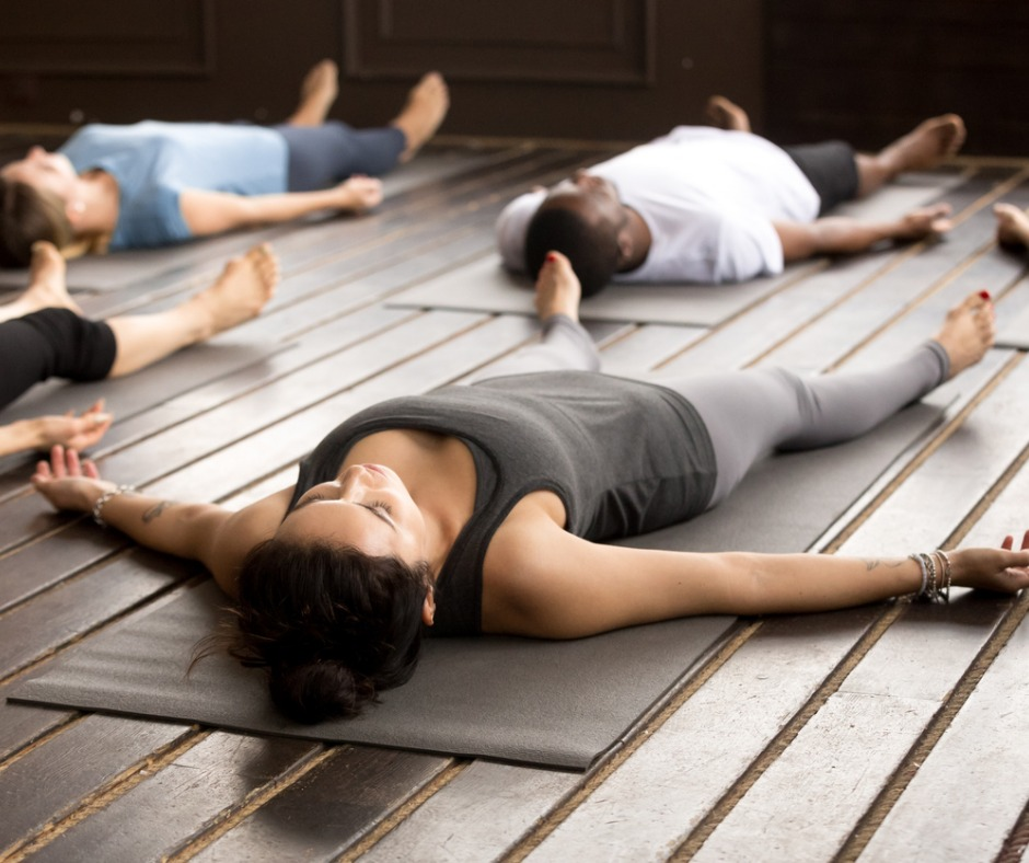 group-of-sporty-people-in-savasana-pose-picture-id922345076.jpg