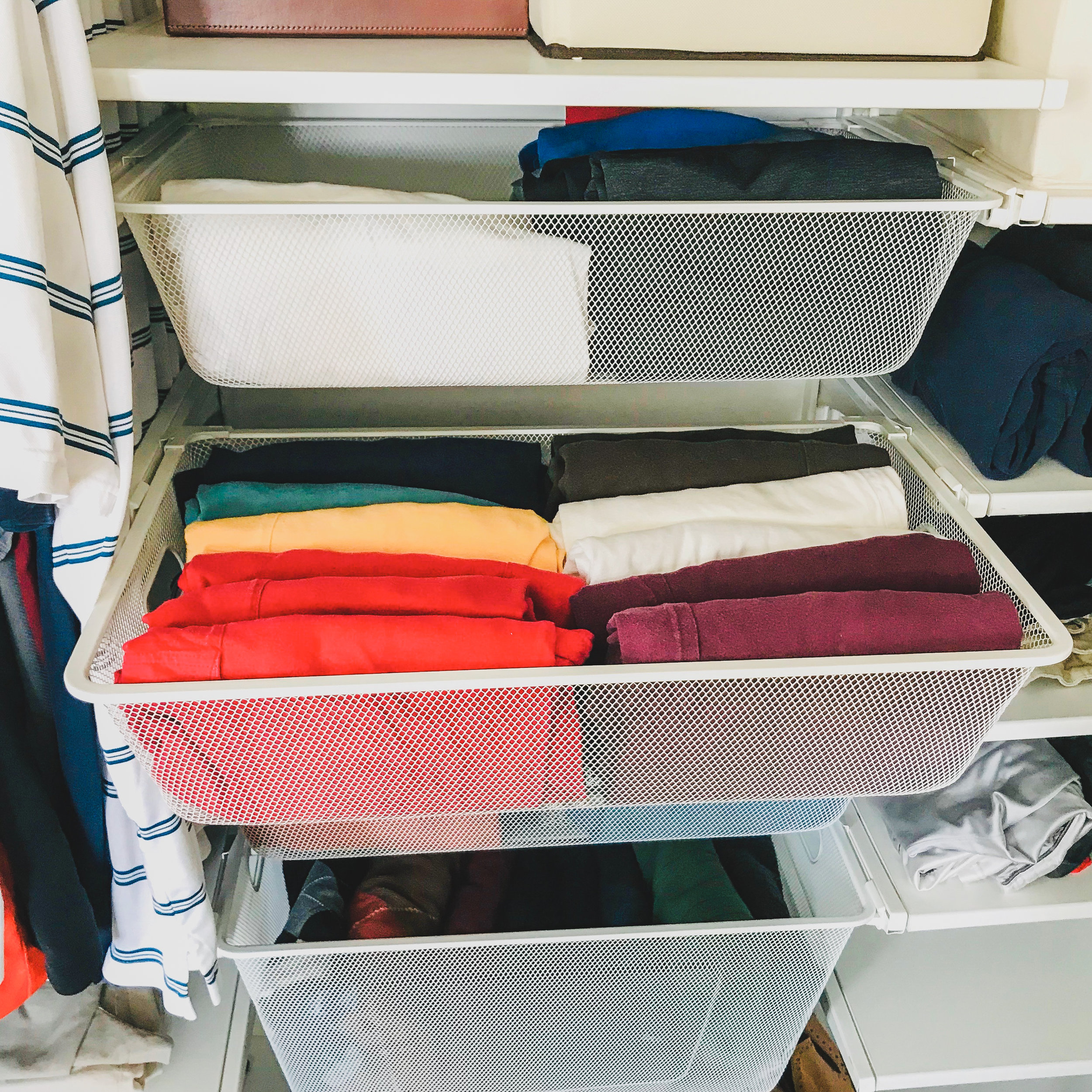 My husband's closet with shirts arranged in a spectrum.