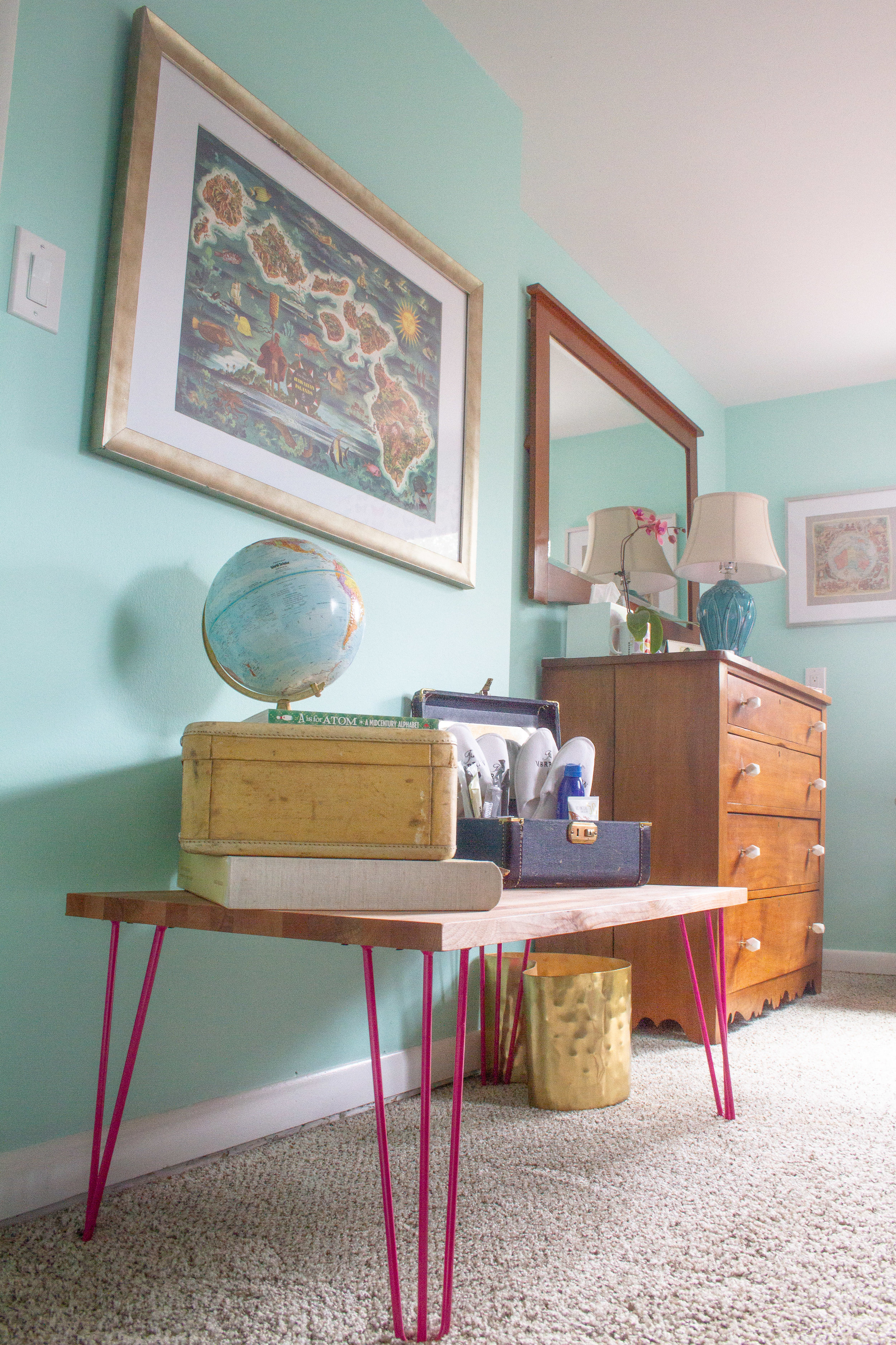 The vintage map inspiration piece hangs just inside the door over a newly-created bench, perfect for holding suitcases.