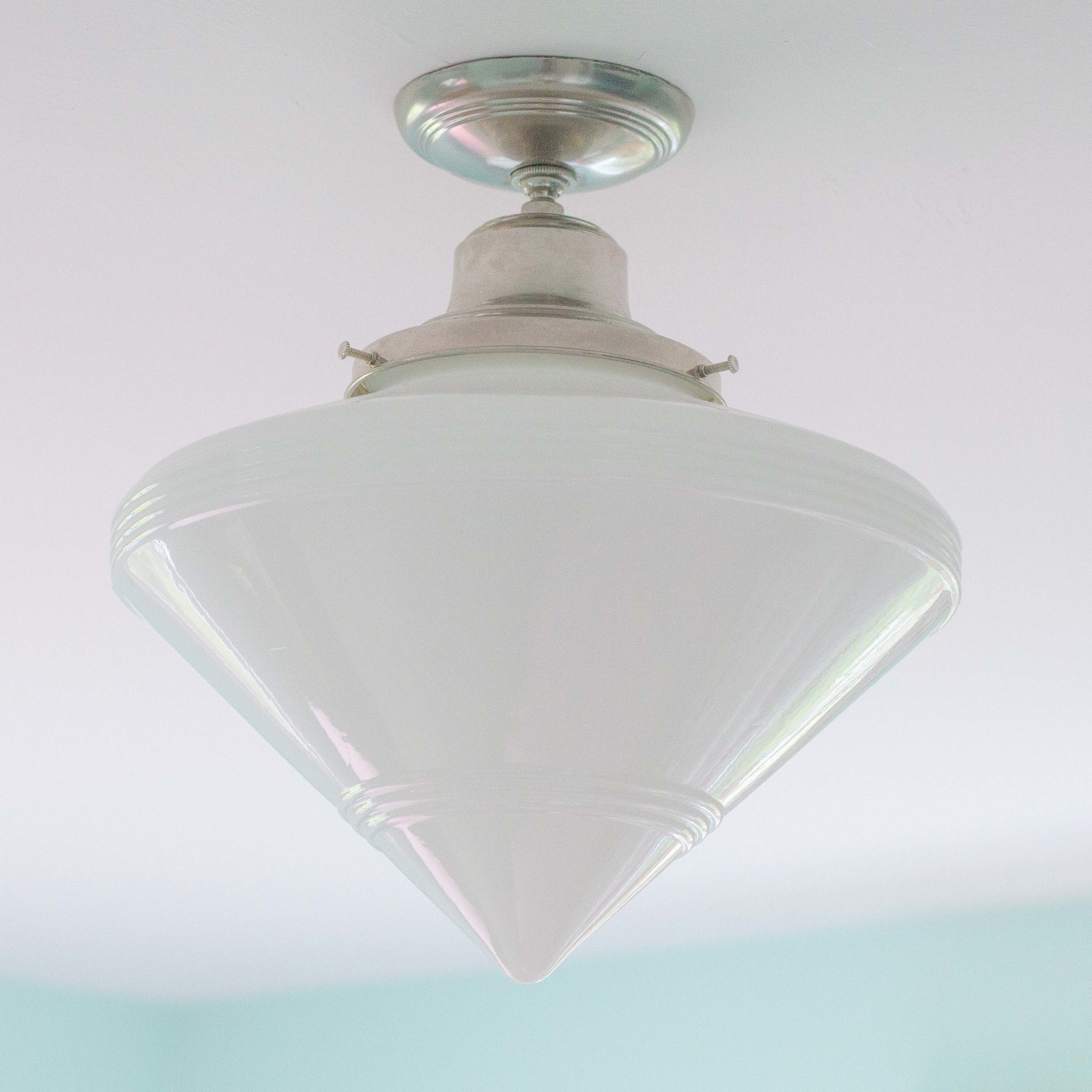 The retro-inspired ceiling fixture with a milk glass shade fits perfectly in this 1958 home.