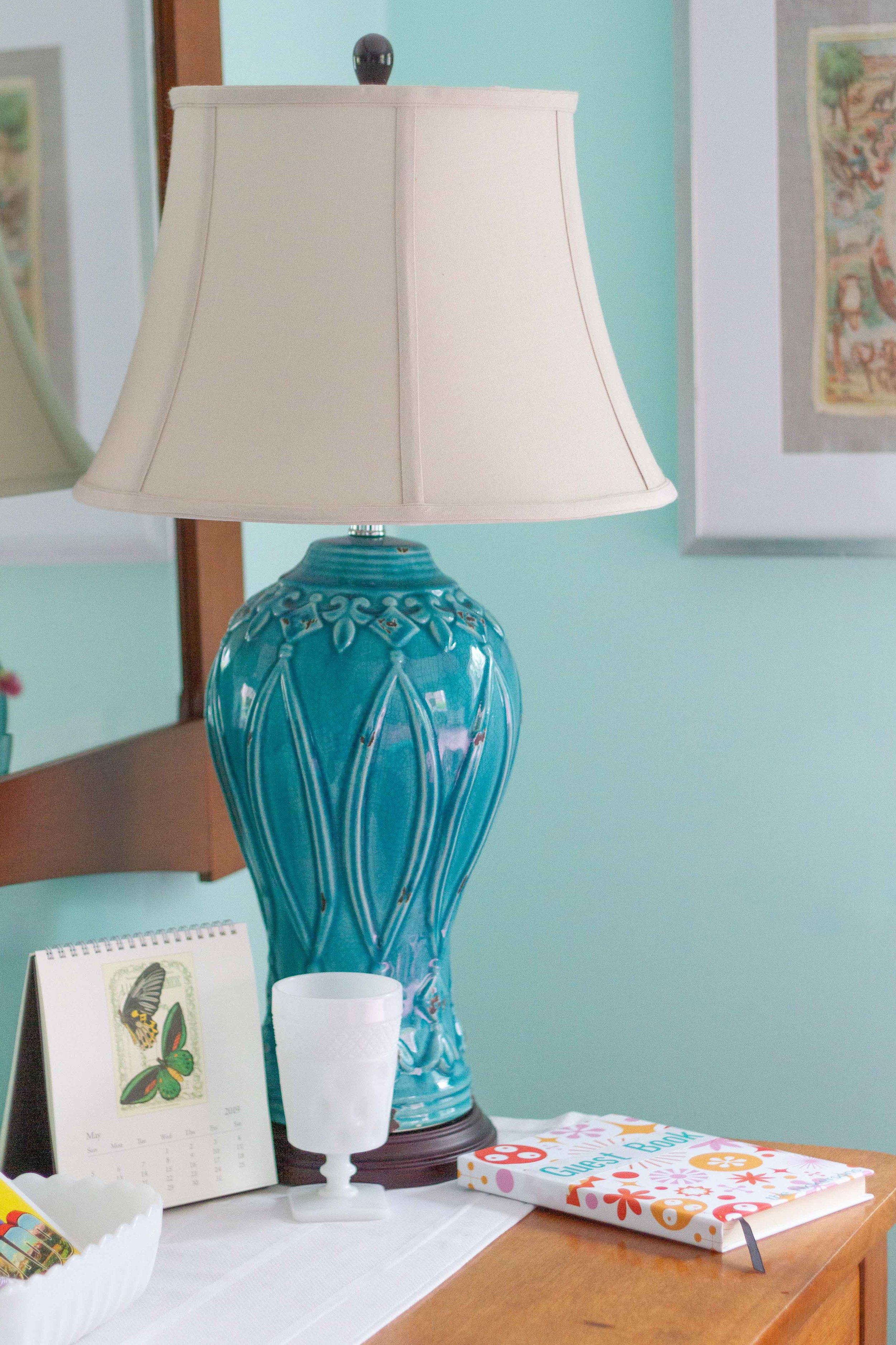 A turquoise porcelain lamp with a classic shade works well on the antique dresser.