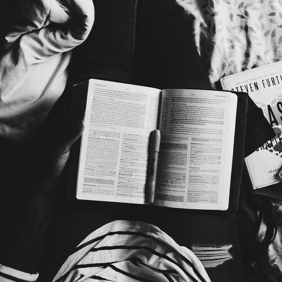 Book laid out on person's lap as they sit in bed