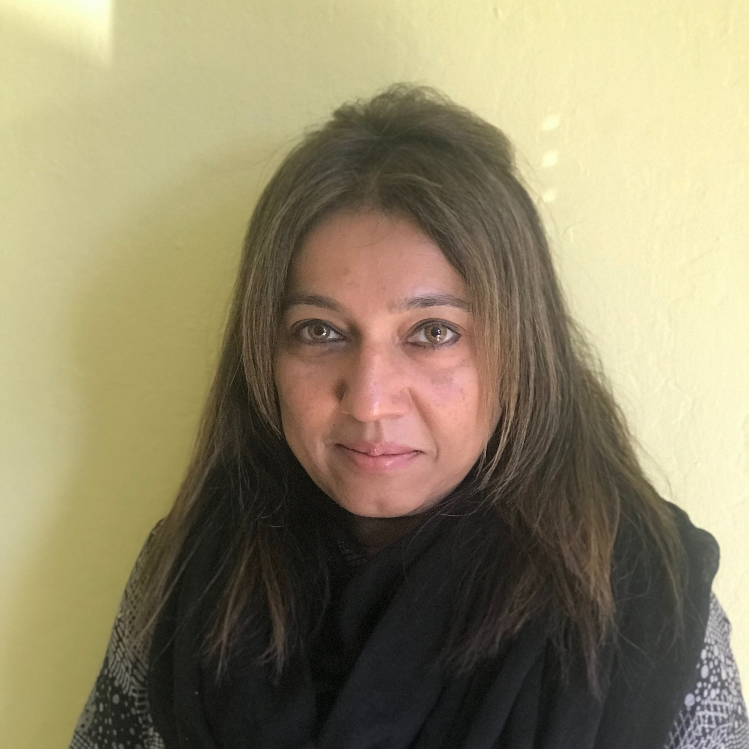 Image of Shakila. She is smiling and standing on front of a yellow background. She is wearing a black and white shirt with a black scarf.
