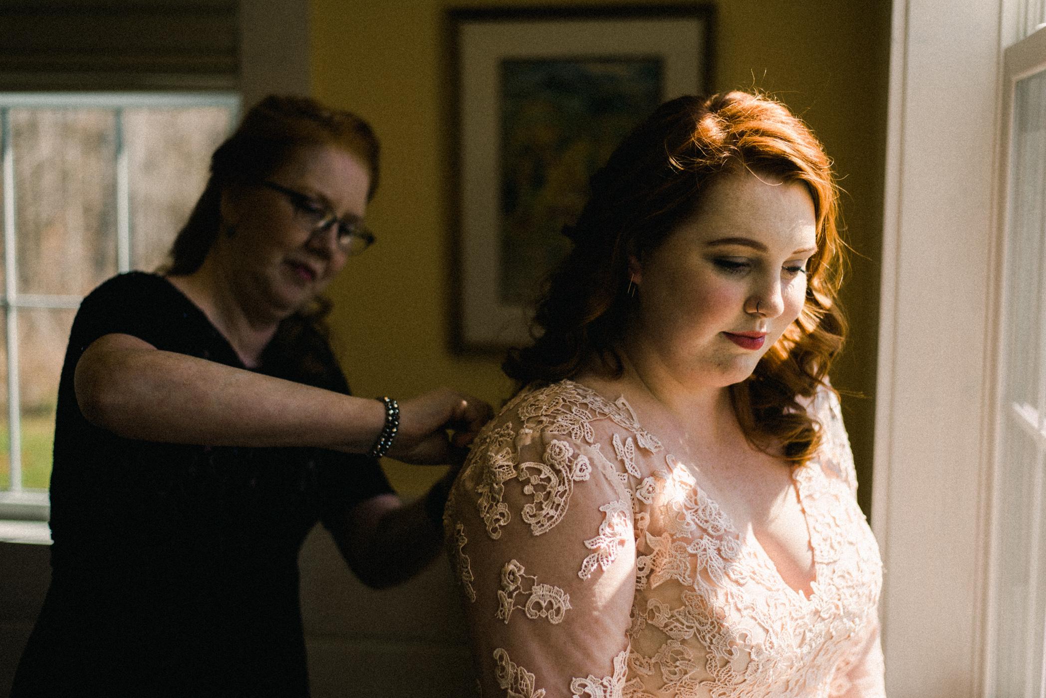 mother helping bride dress
