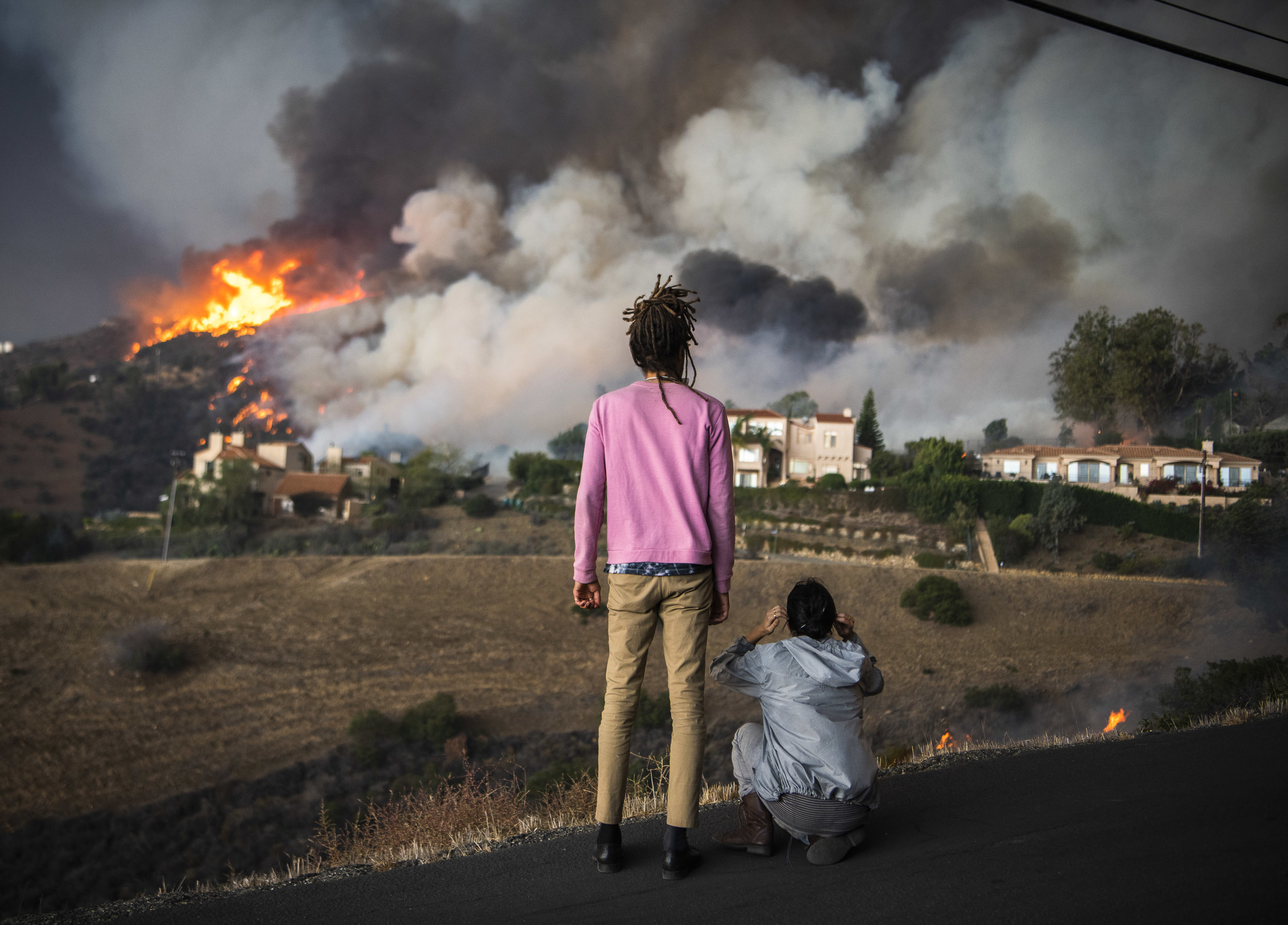 Malibu residents Jordan Pope and Sara Daoud watch in terror as flames engulf their home on Las Trancas Canyon Road as the Woolsey Fire burns through in Malibu Friday November 9th. Minutes later the area was engulfed by a rotating column of fire. Miraculously the home survived while structures around it were destroyed.