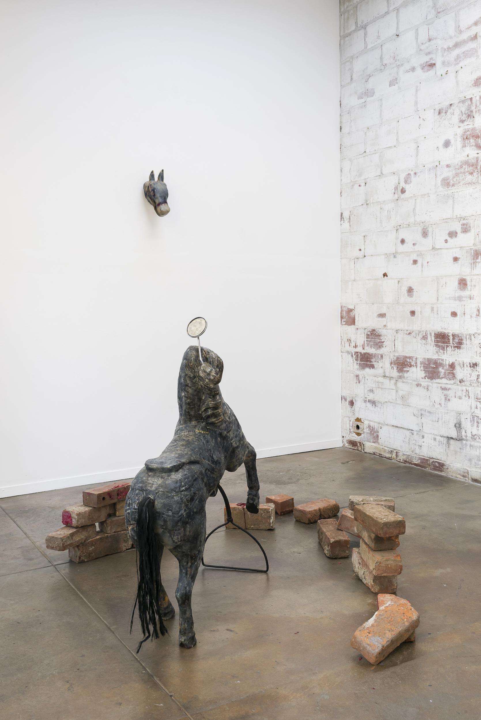Bri Williams,  Medusa , 2018. Carousel horse, soap, bike mirror, red wax, bricks