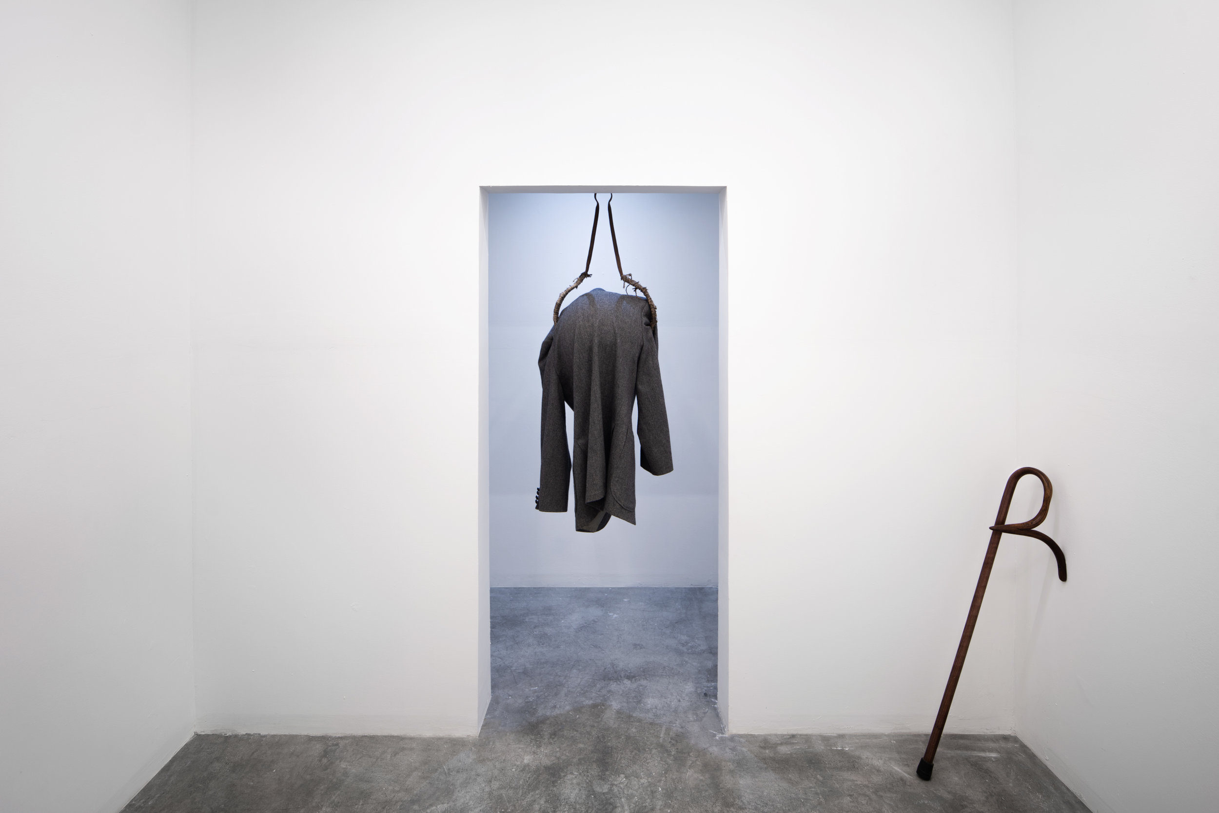 Moch Hahn,  You're Late , 2018, Found suit coat, metal, rope, plastic globe 46'' x 17'' x 14''