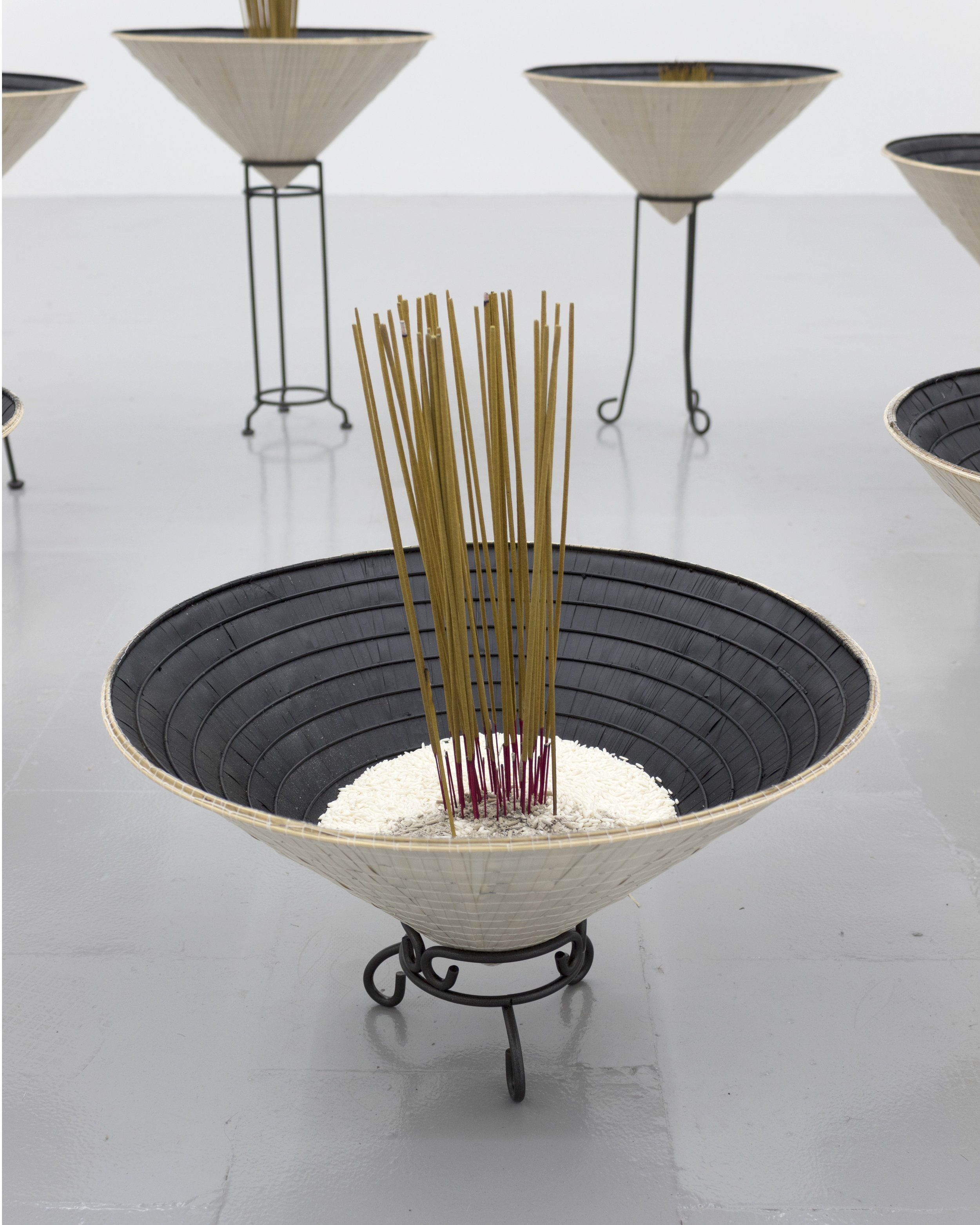 Millian Giang Lien Pham,  Reforge: 9 Phases (One),  2019. Conical hat, sweet rice, incense, metal stand