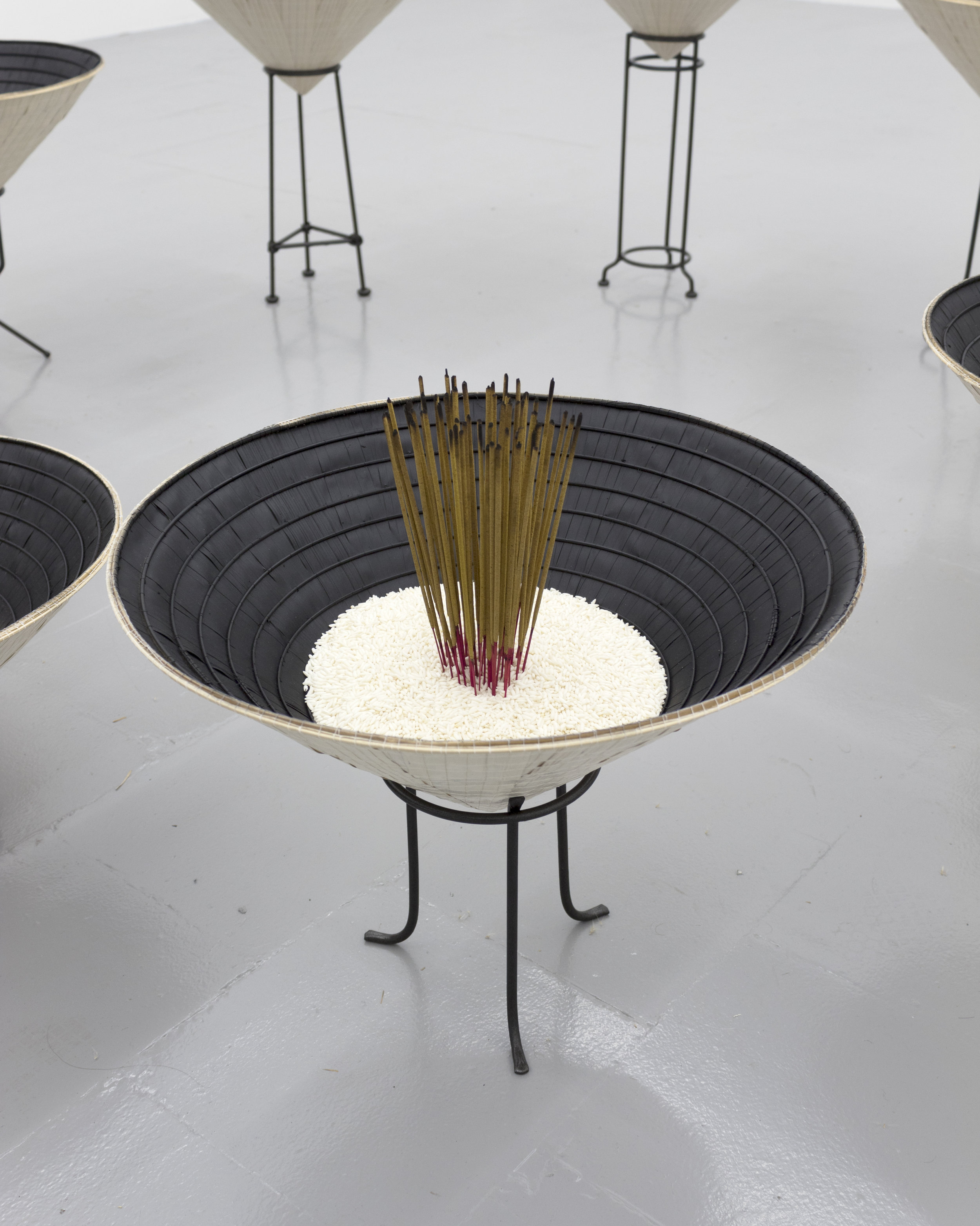 Millian Giang Lien Pham,  Reforge: 9 Phases (Two),  2019. Conical hat, sweet rice, incense, metal stand