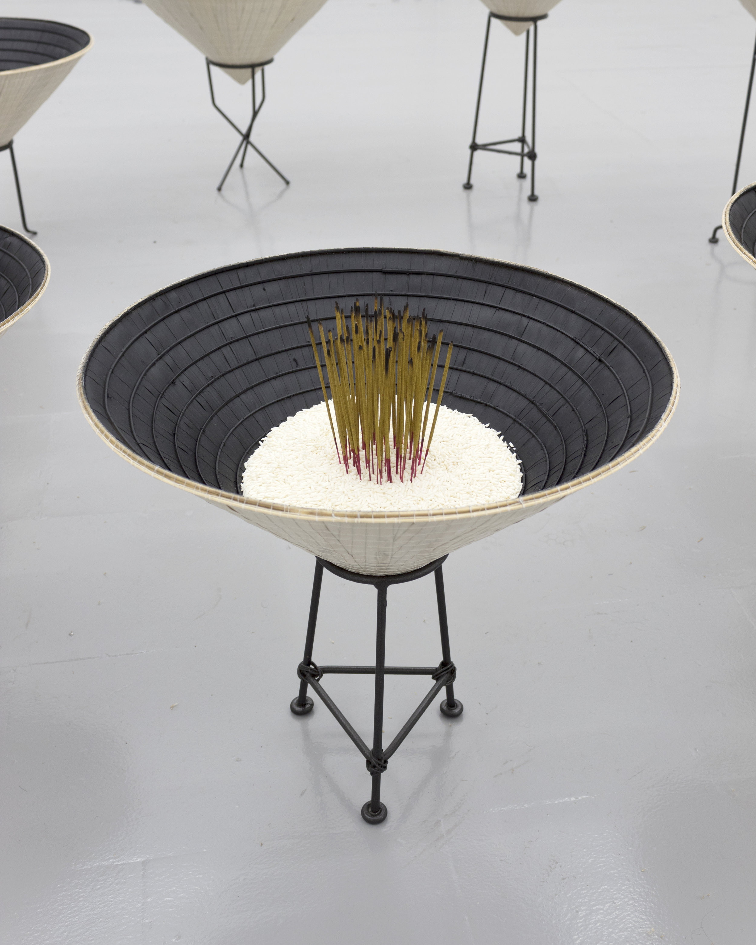 Millian Giang Lien Pham,  Reforge: 9 Phases (Three),  2019. Conical hat, sweet rice, incense, metal stand