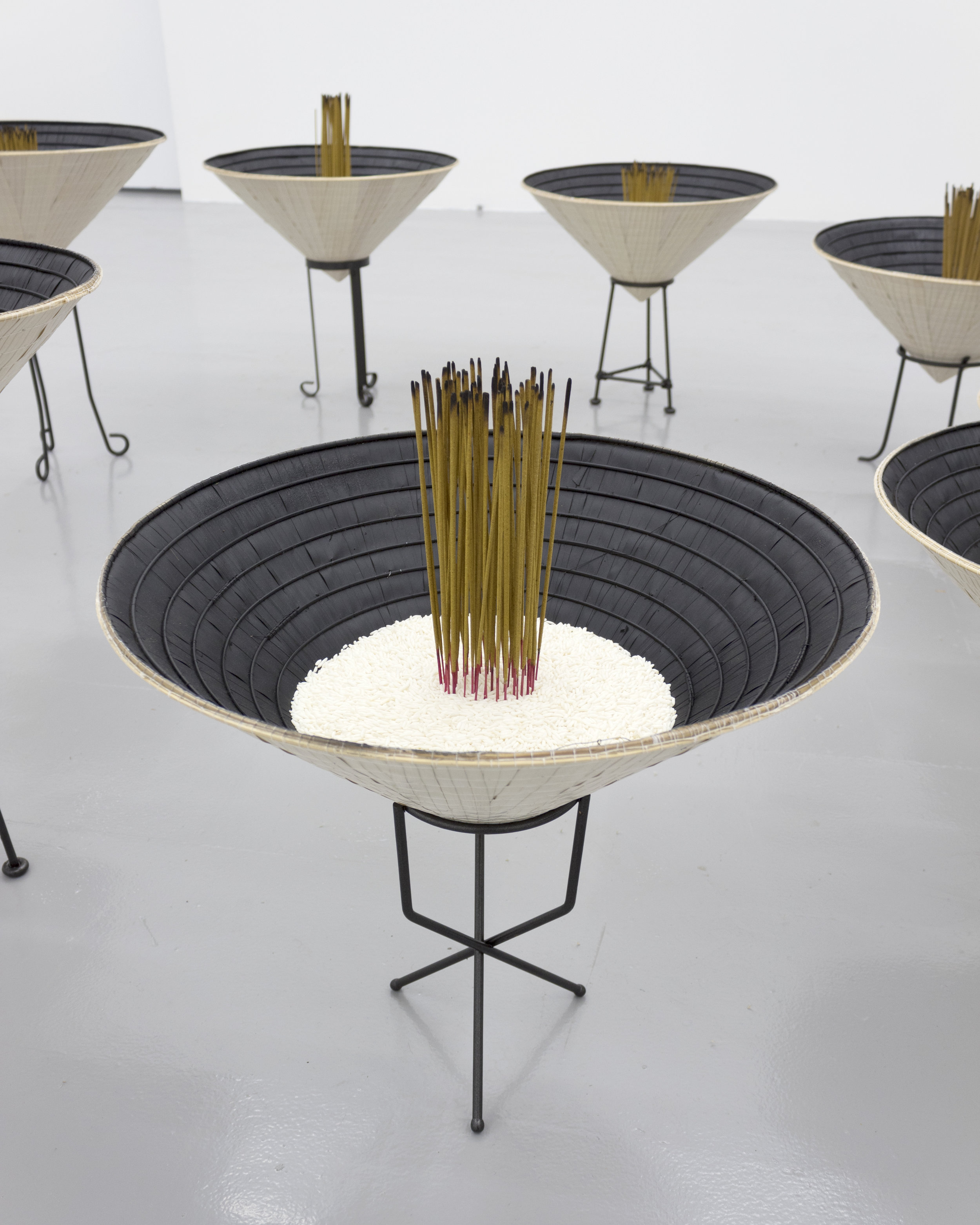 Millian Giang Lien Pham,  Reforge: 9 Phases (Eight),  2019. Conical hat, sweet rice, incense, metal stand