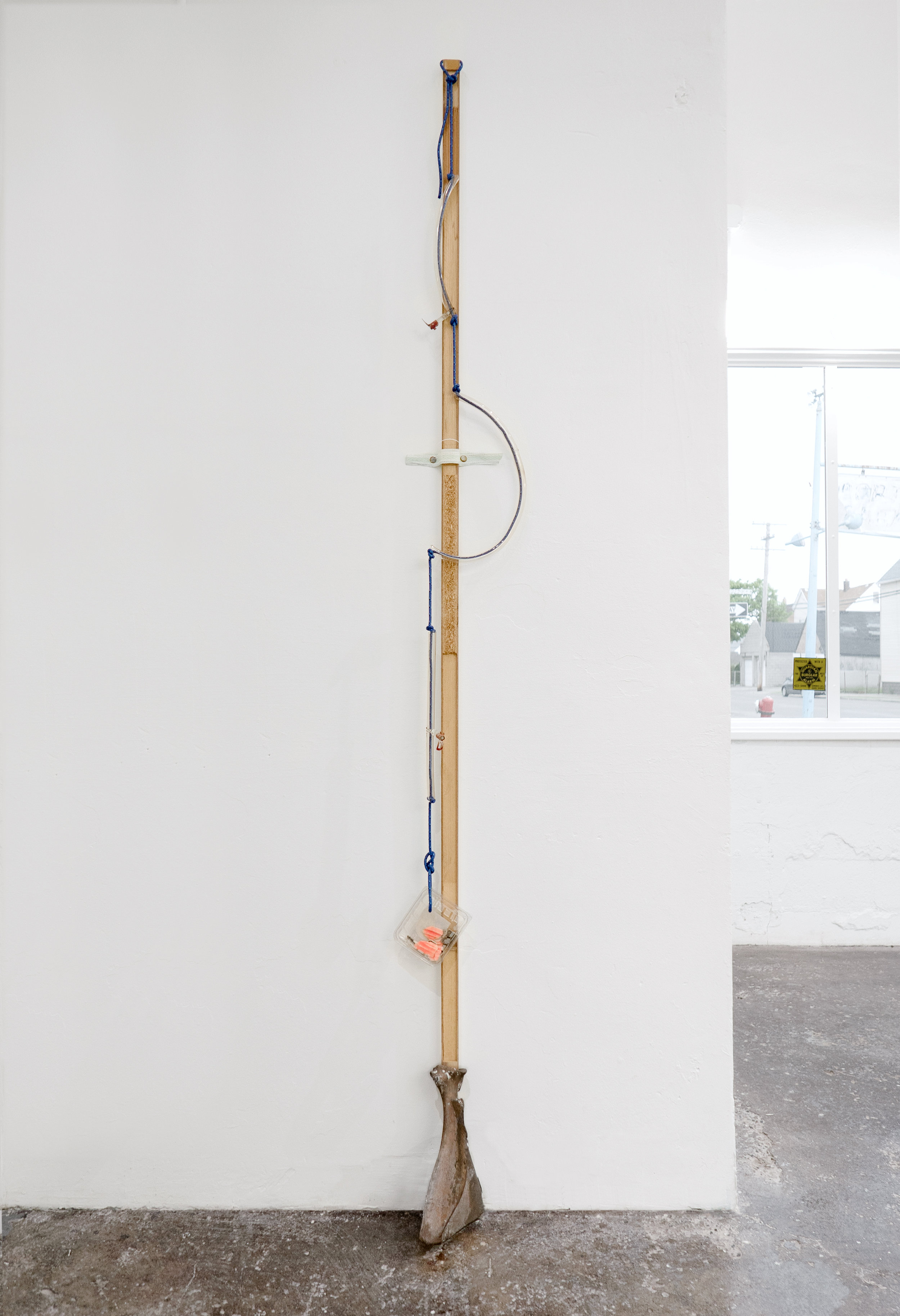Matt Siegel,  N , 2019, Raw bronze, hollow core door, accessory cord, neon glass tubing (sourced: abandoned China Buffet, Evanston, WY), blueberry container, found objects, wind, 92 x 8 x 5 in