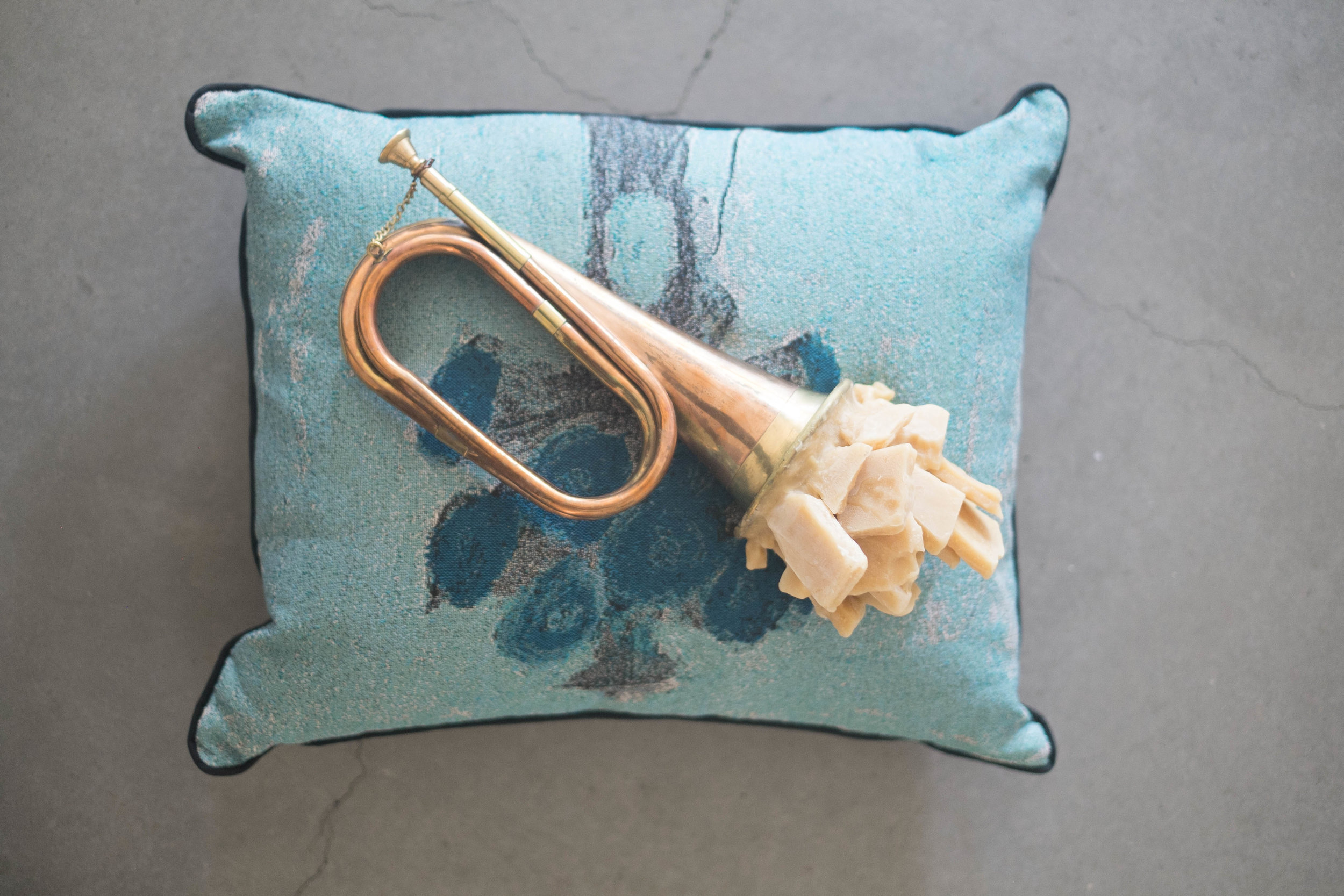 Lest They Listen , 2019, Miniature bugle, cotton Jacquard tapestry pillow, beeswax