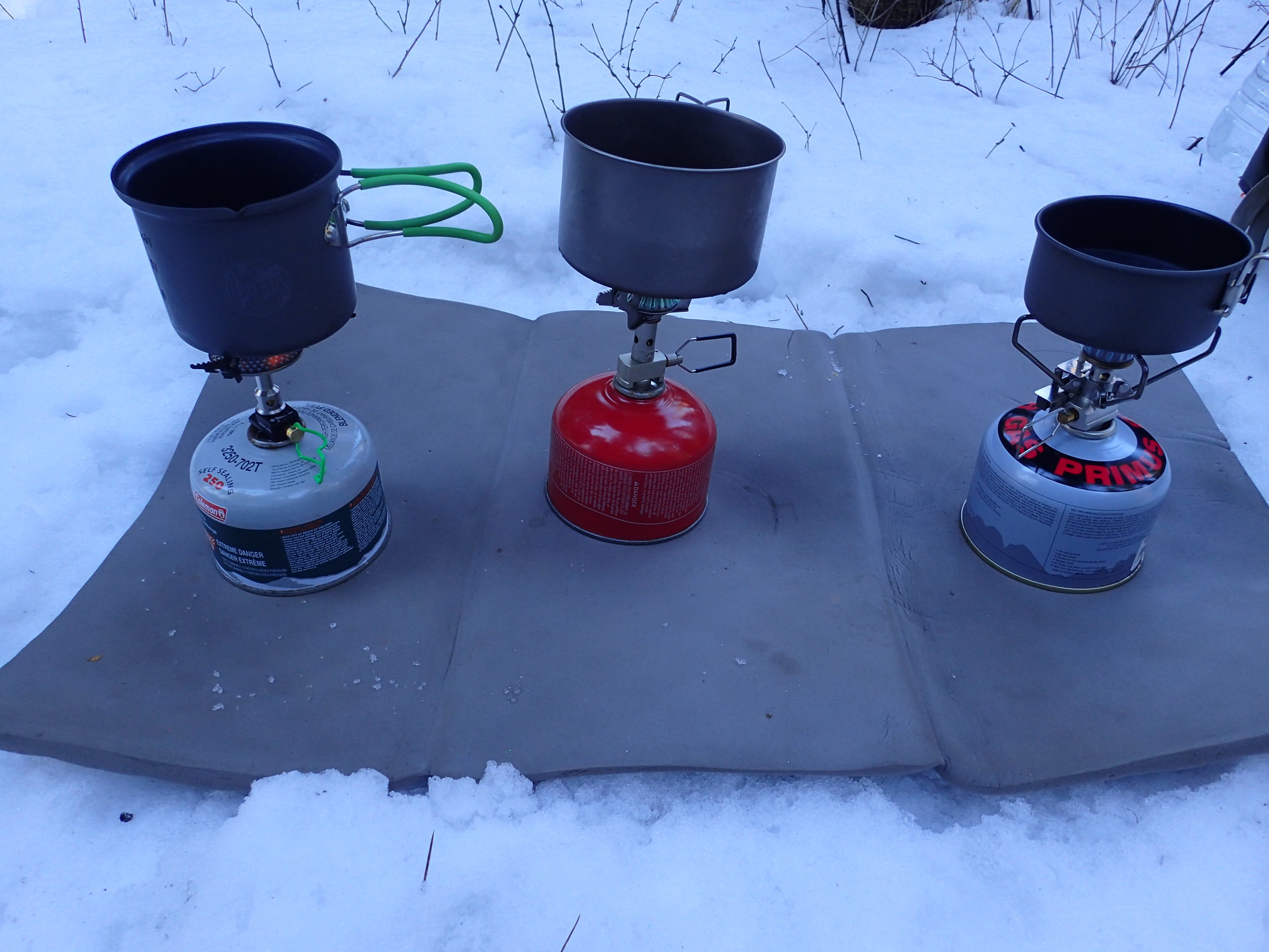Three different cookpots on three different stoves. Stove testing in northern Idaho in winter.   Photo by Liz Thomas.