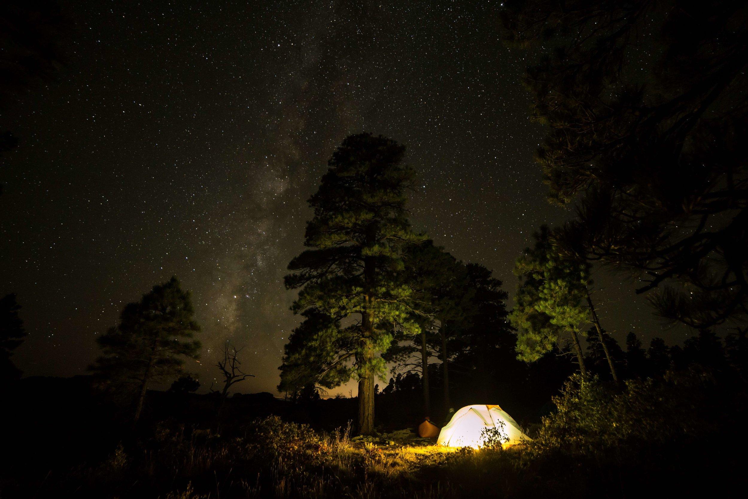 An illuminated tent under a starry night sky.