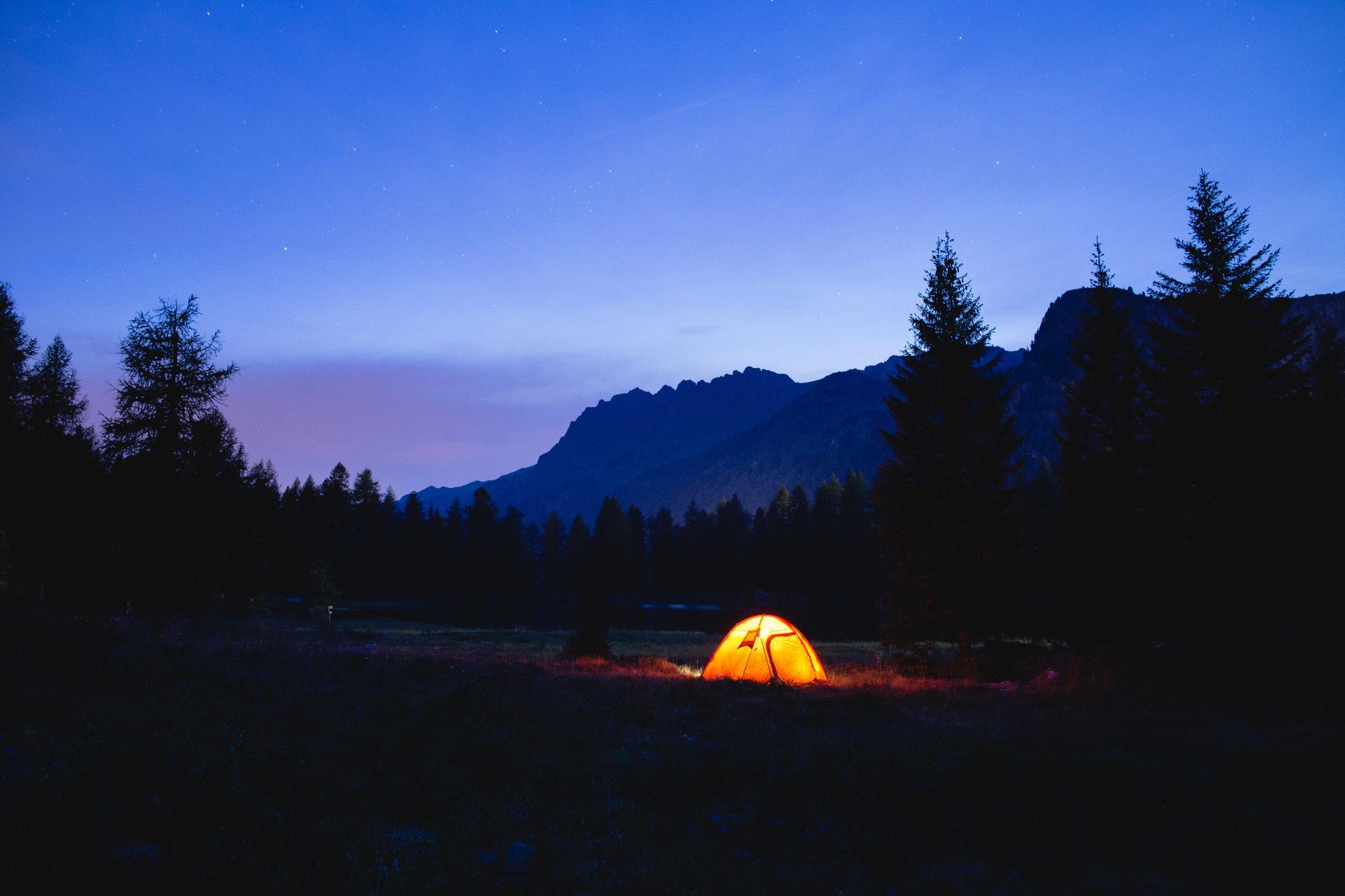 An illuminated tent under a darkening sky.