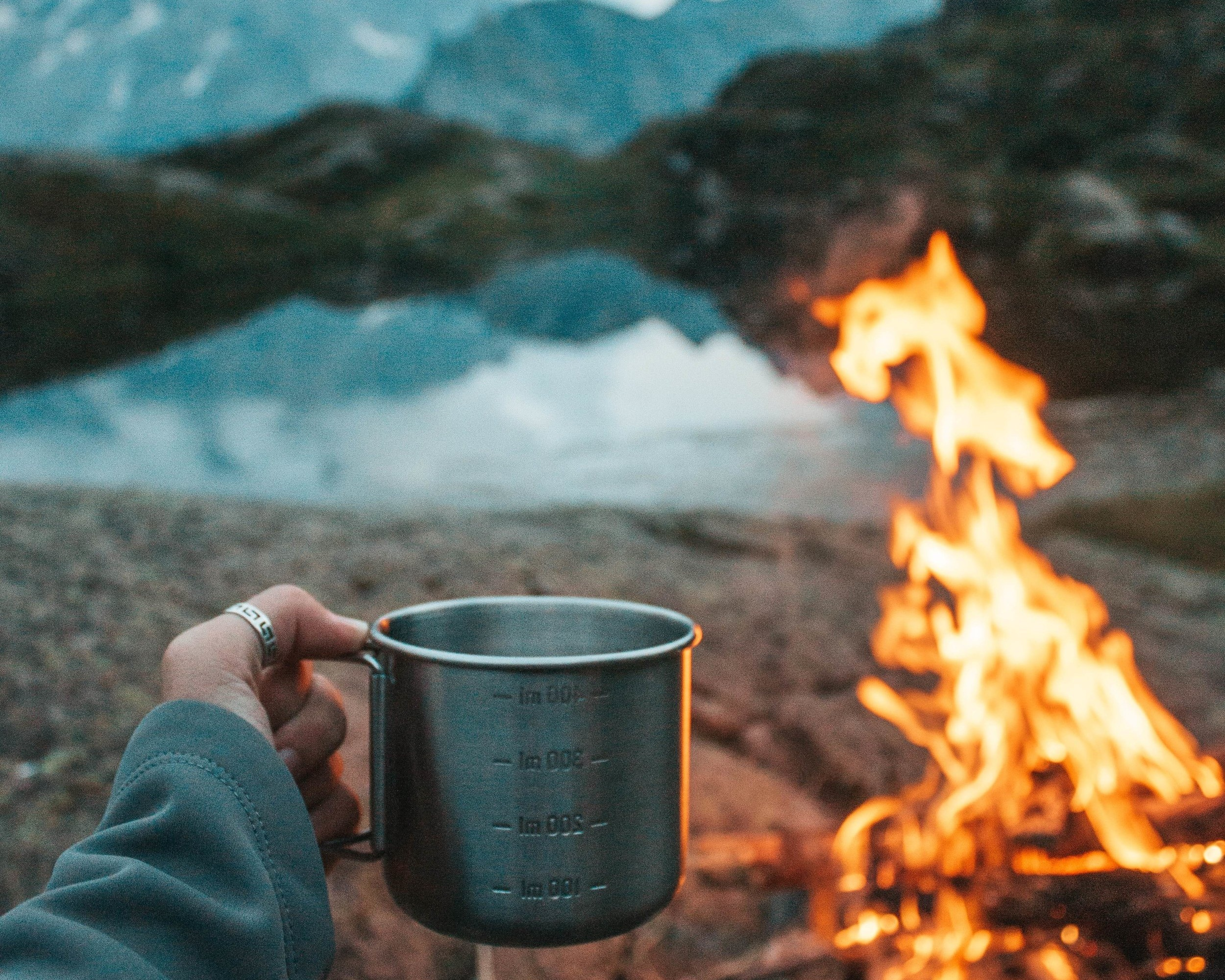A person holding a mug in front of a camp fire. Caution: not all cookpots can go directly over a fire.