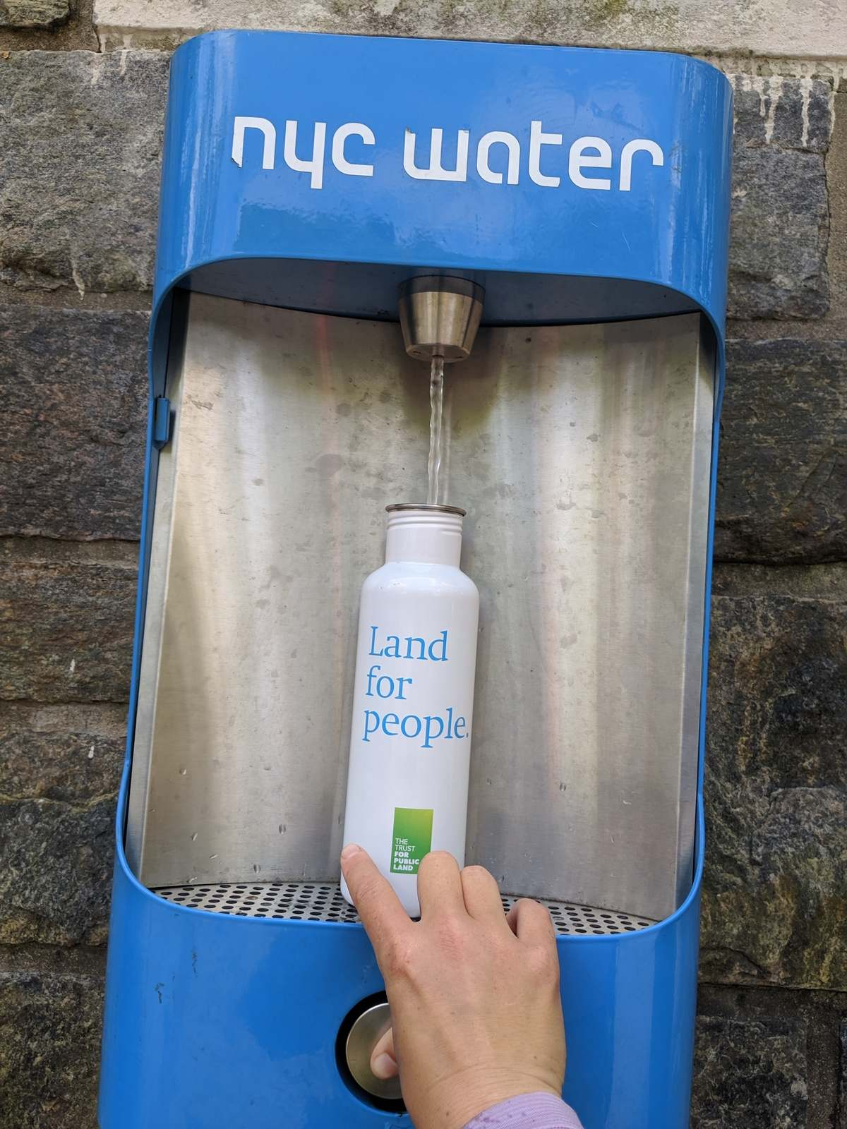 The Hydro Flask 24 ounce insulated water bottle with the Trust for Public Land logo, getting filled at a water station in New York City.