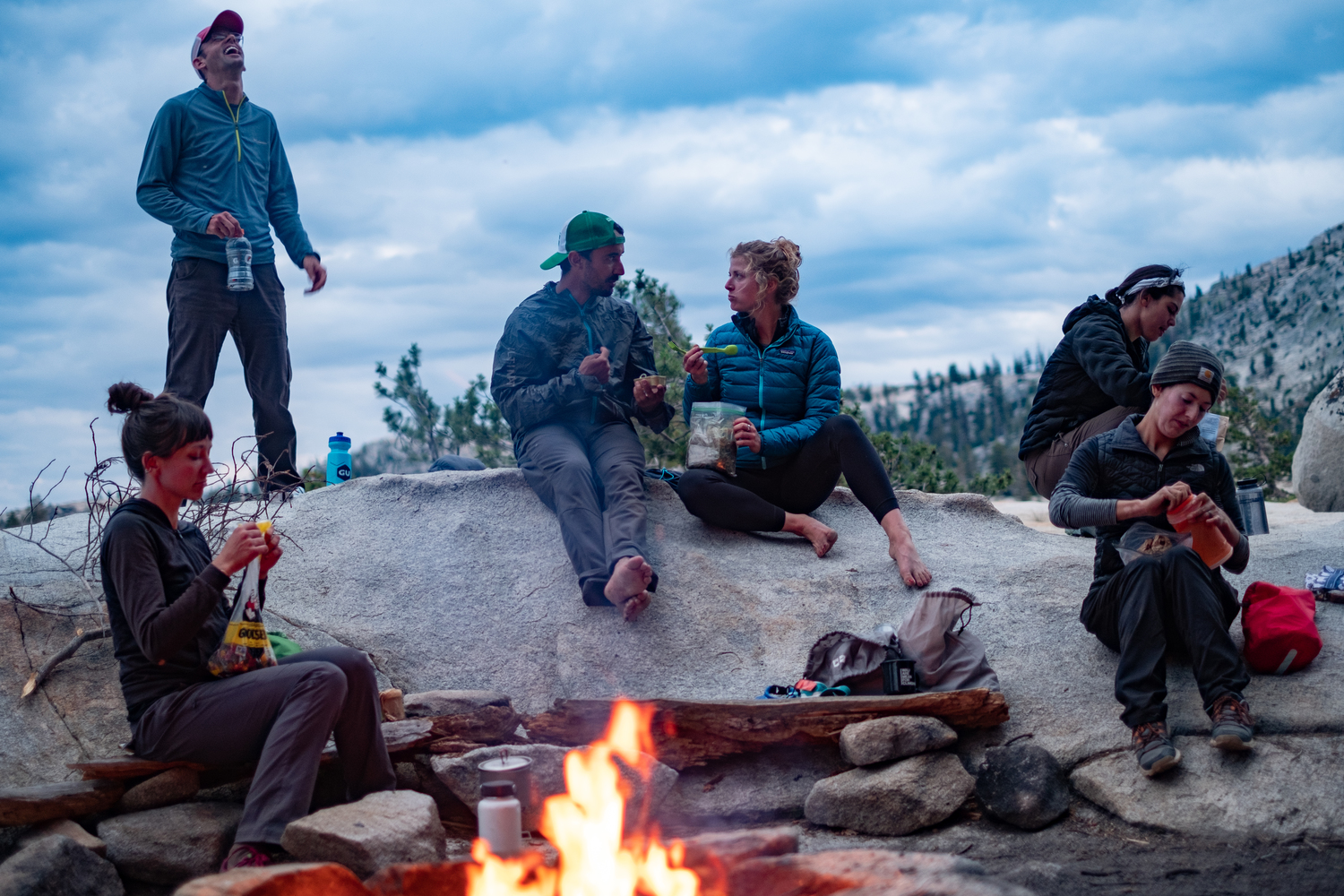 Six friends gather around a campfire with camping dinners. They are cooking meals on backpacking stoves. Five people are on a granite rock and one person sits on a log. A mountain is in the background.
