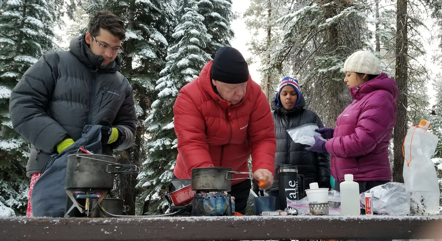 A variety of stoves being tested on a snowy cold morning.